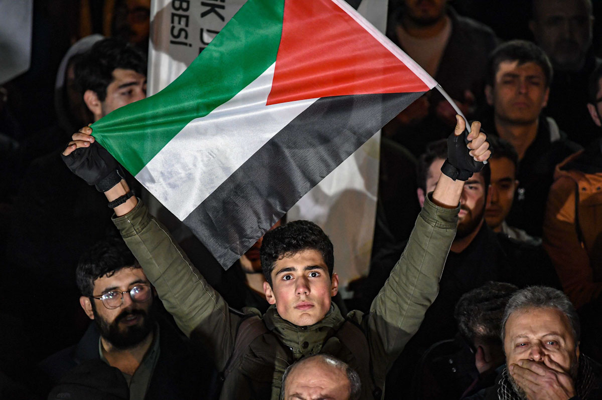 A man holds a flag of Palestine as protesters take part in a demonstration in front of the US consulate in Istanbul on January 29, 2020, to protest against the US peace plan. (AFP)