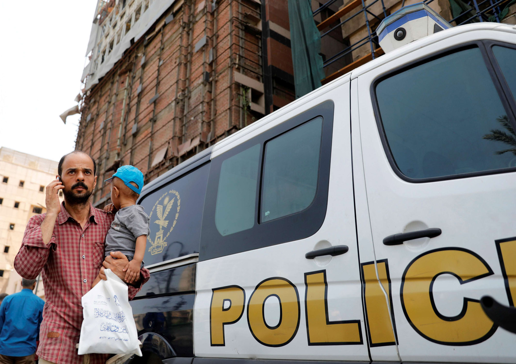 An Egyptian man carries his son as he walks past a police car in Cairo. (Reuters)