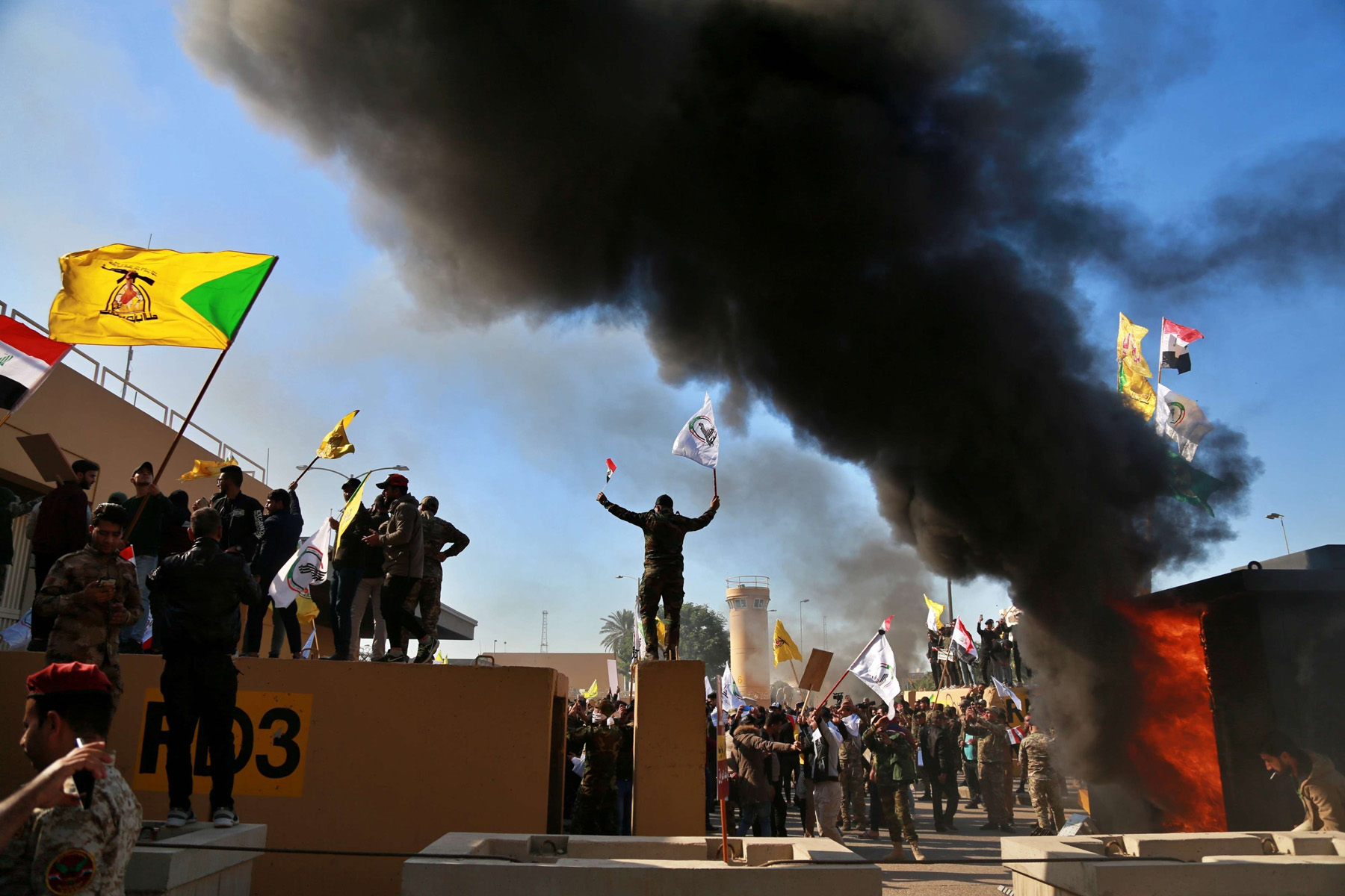 In this Tuesday, Dec 31, 2019, file photo, protesters burn property in front of the U.S. embassy compound, in Baghdad, Iraq. (AP)