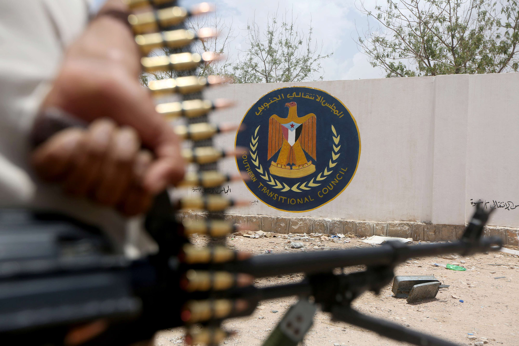 A Yemeni government soldier holds a weapon as he stands by an emblem of the Southern Transitional Council at the council's headquarters in Ataq, last August. (Reuters)