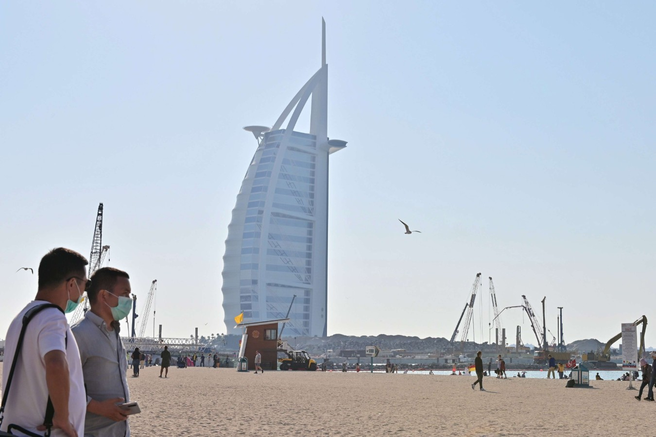 Tourists wearing surgical are pictured on a beach next to Burj Al Arab on January 29. (AFP)