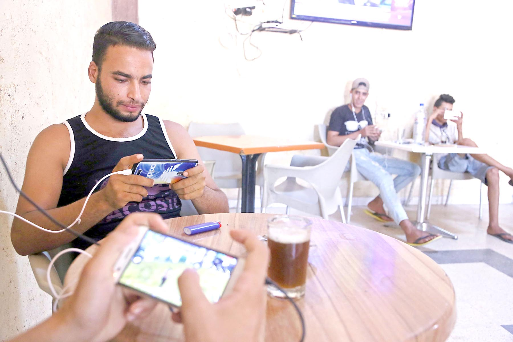 Idle. Tunisian youths play on their mobile phones in the central Tunisian town of Sidi Bouzid.        (AFP)