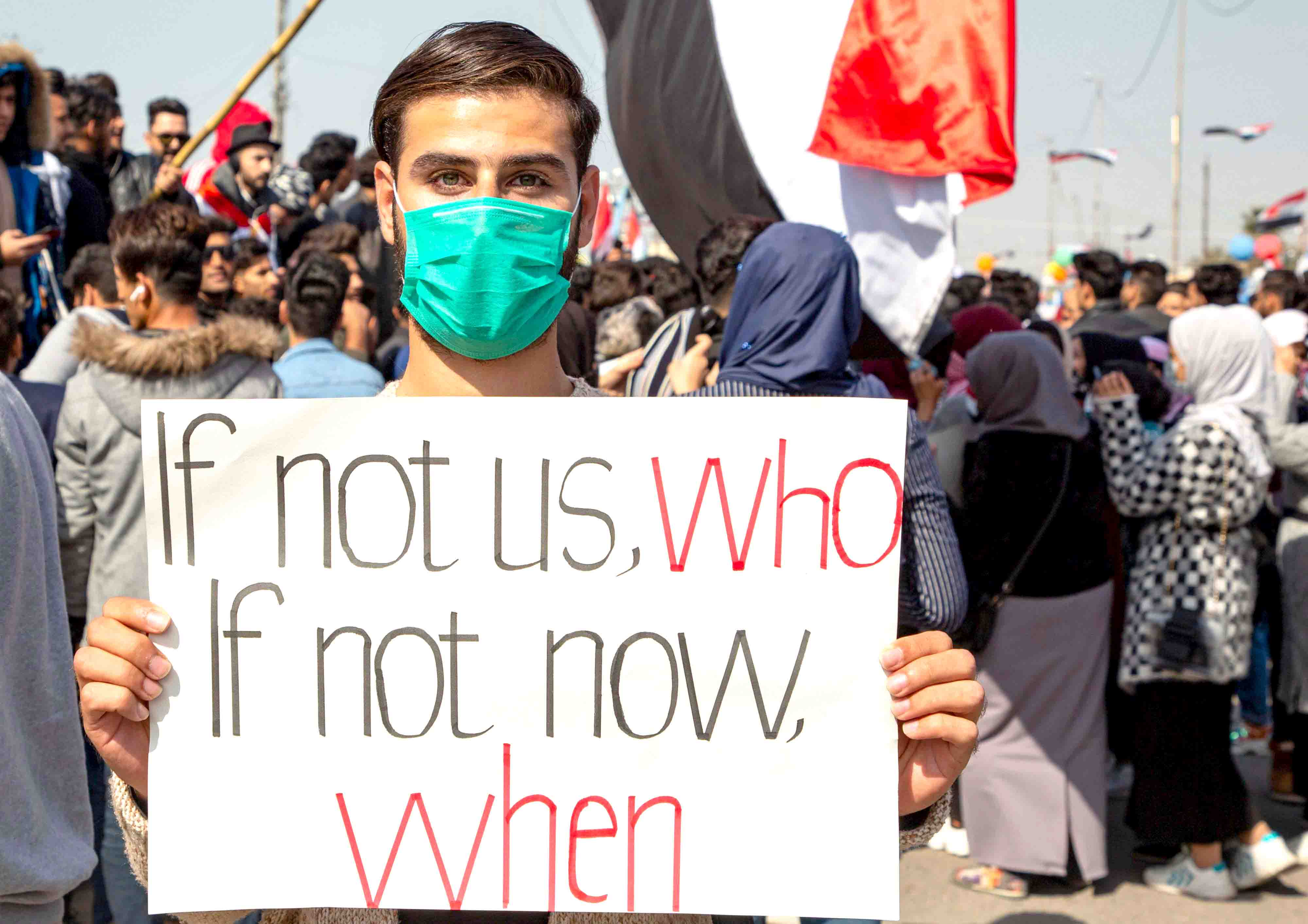 An Iraqi holds a placard during an anti-government protest in Basra, February 11. (AFP)