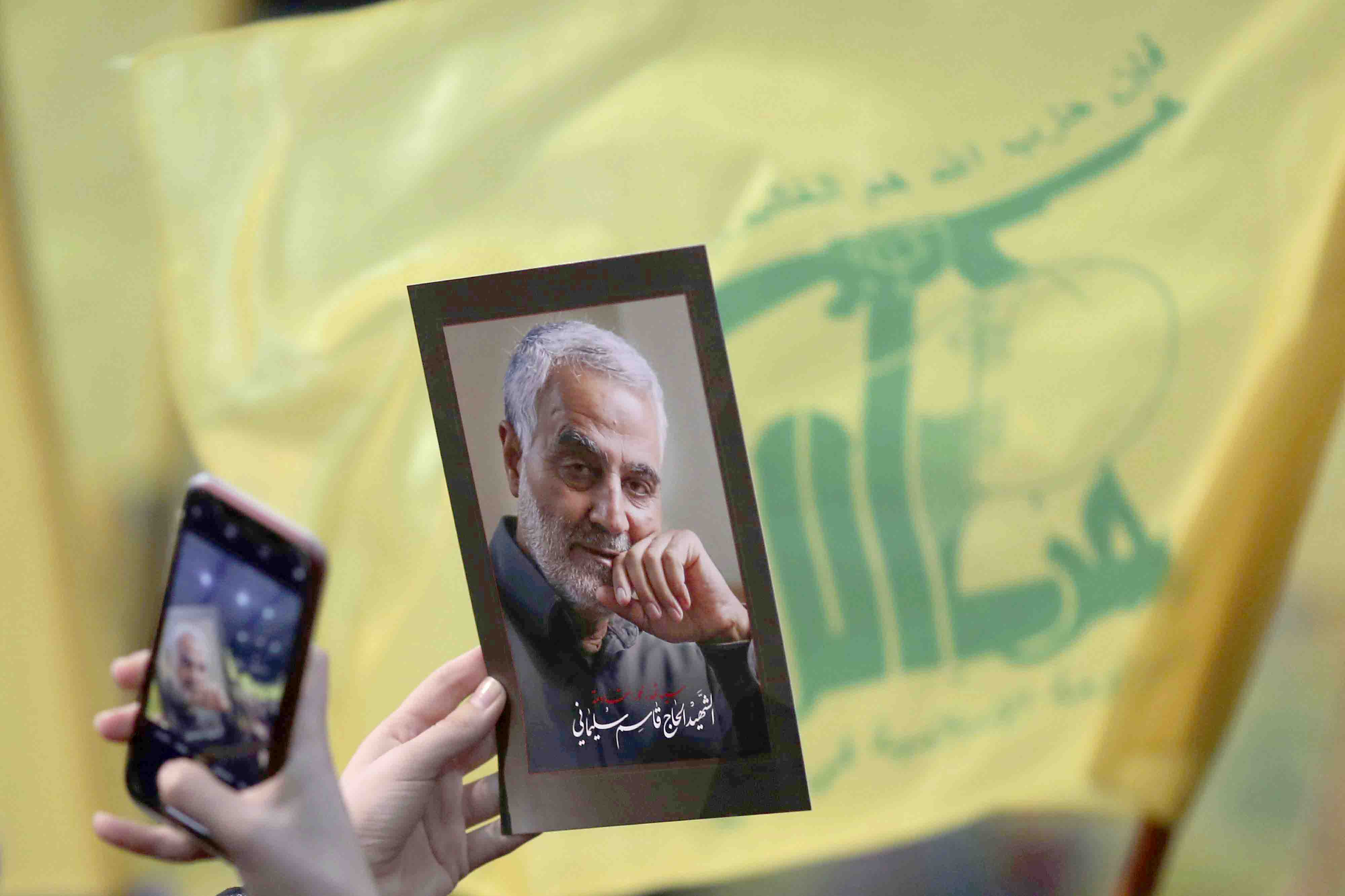A Hezbollah supporter uses her mobile phone to take a picture of photo of slain Islamic Revolutionary Guard Corps' Major-General Qassem Soleimani during a ceremony in the southern suburb of Beirut, February 16. (AP)