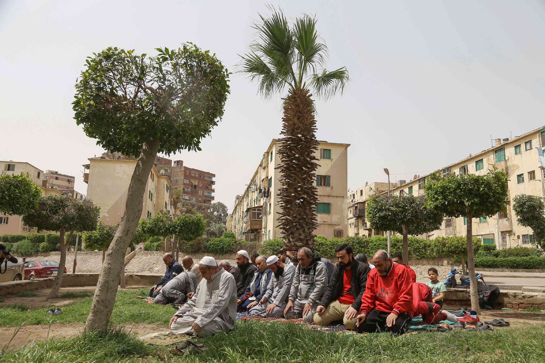"Egyptian men perform the ""Zuhr (noon) prayer"" at a public park in the capital Cairo, on March 27, after a decision from the Ministry of Awqaf (religious emdowments) to close mosques and suspend Friday prayers amid the COVID-19 pandemic. (AFP)"