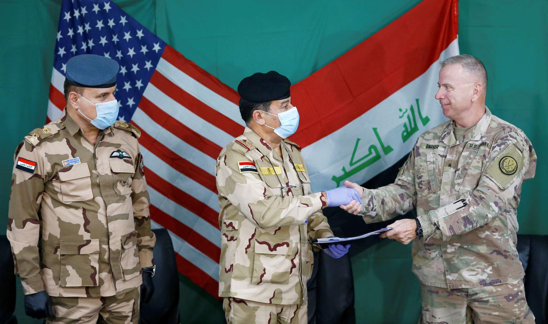 US Brigadier General Vincent Barker shakes hands with Iraqi General Mohammed Fadel, as he wears face mask and gloves, following the outbreak of coronvavirus disease, during the handover of Qayyarah Airfield West from US-led coalition forces to Iraqi Security Forces, in Mosul, Iraq, March 26. (Reuters)