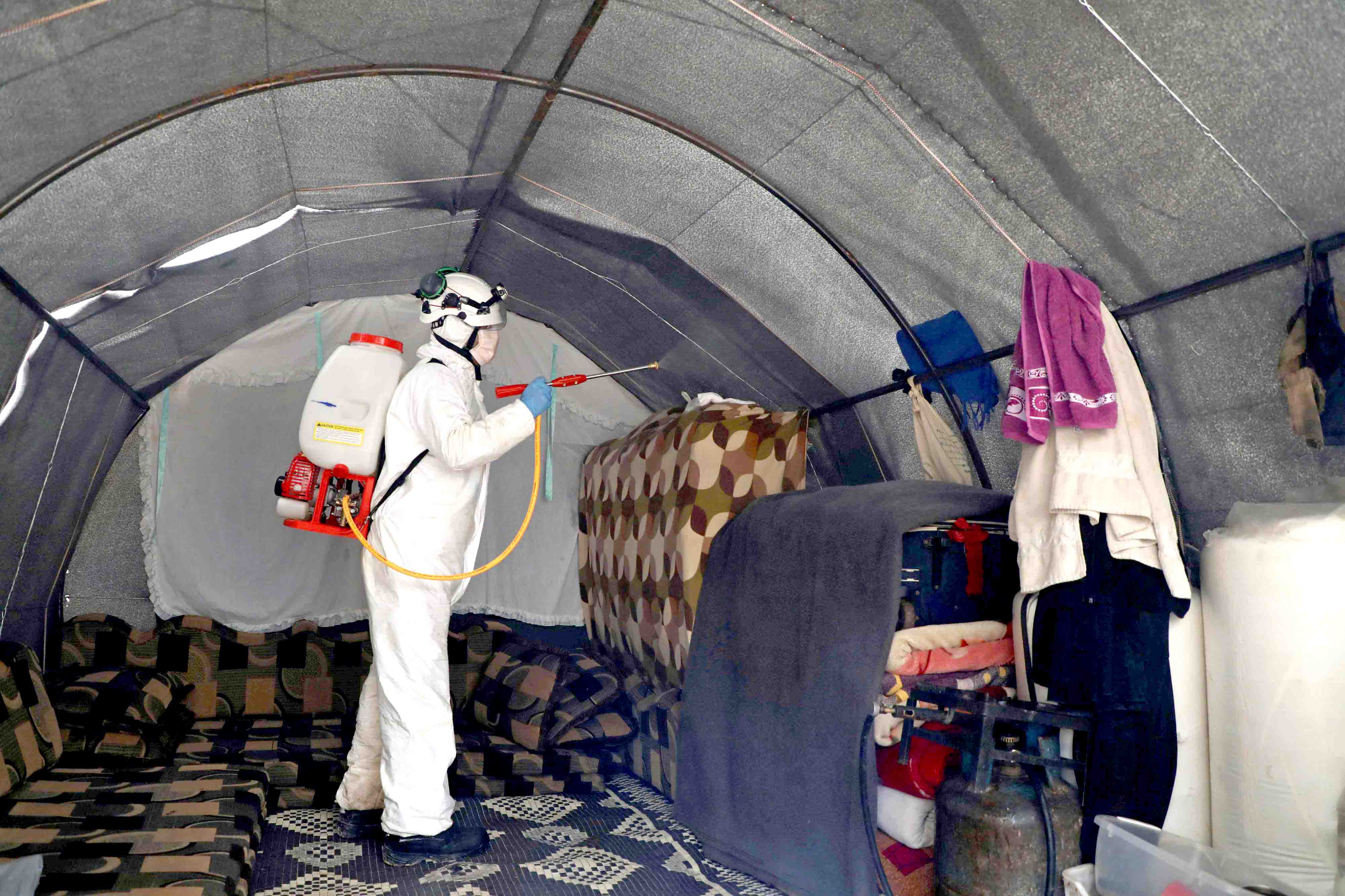 "A member of the Syrian ""White Helmets"" disinfects a tent in the Kafr Lusin camp for the displaced by the border with Turkey, in Syria's province of Idlib, as part of efforts to prevent the spread of coronavirus, March 24. (AFP)"