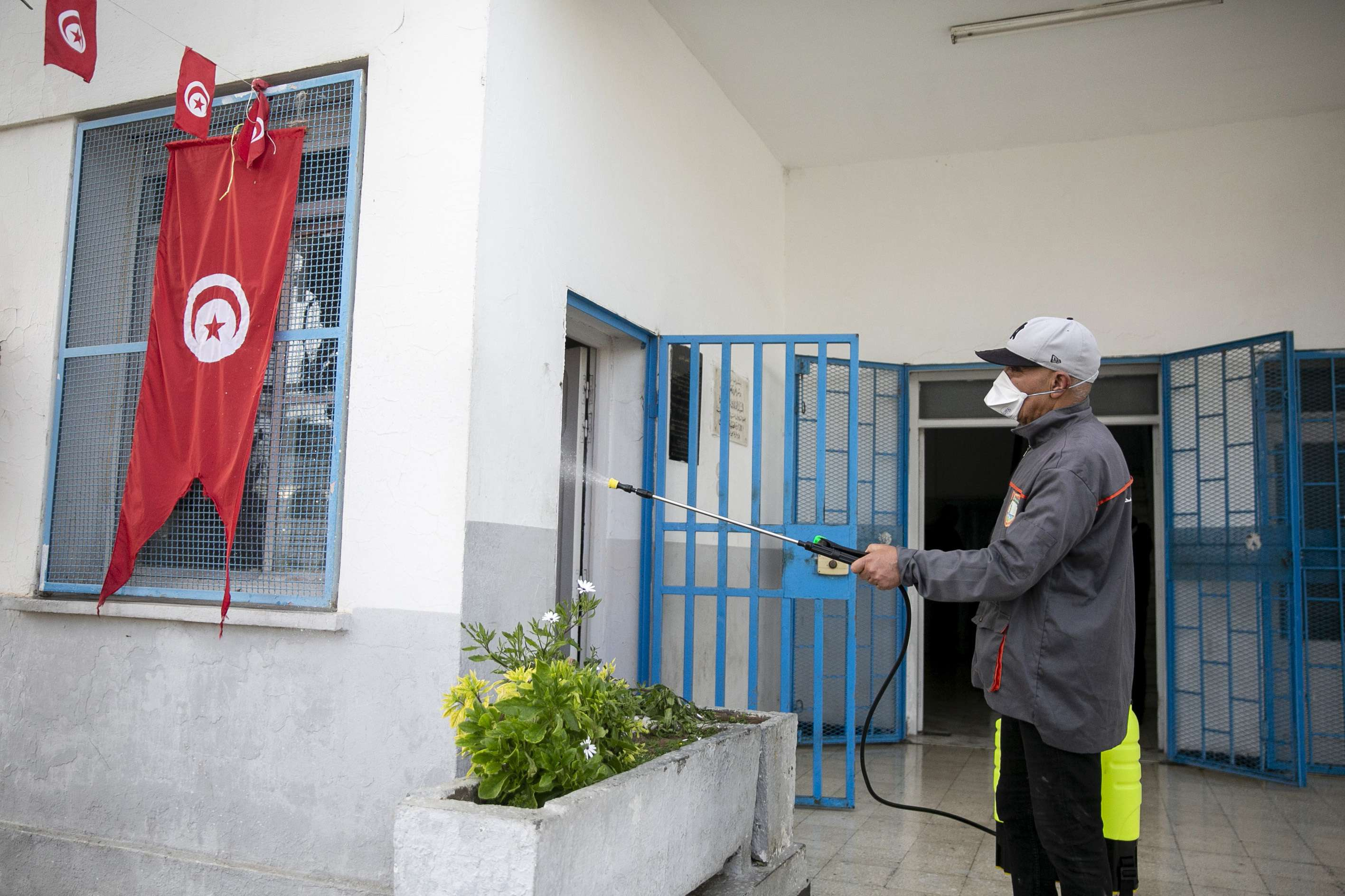 A Tunisian public health worker disinfects an office of an administration in Tunis, Tunisia, Friday, March, 13. (AP)