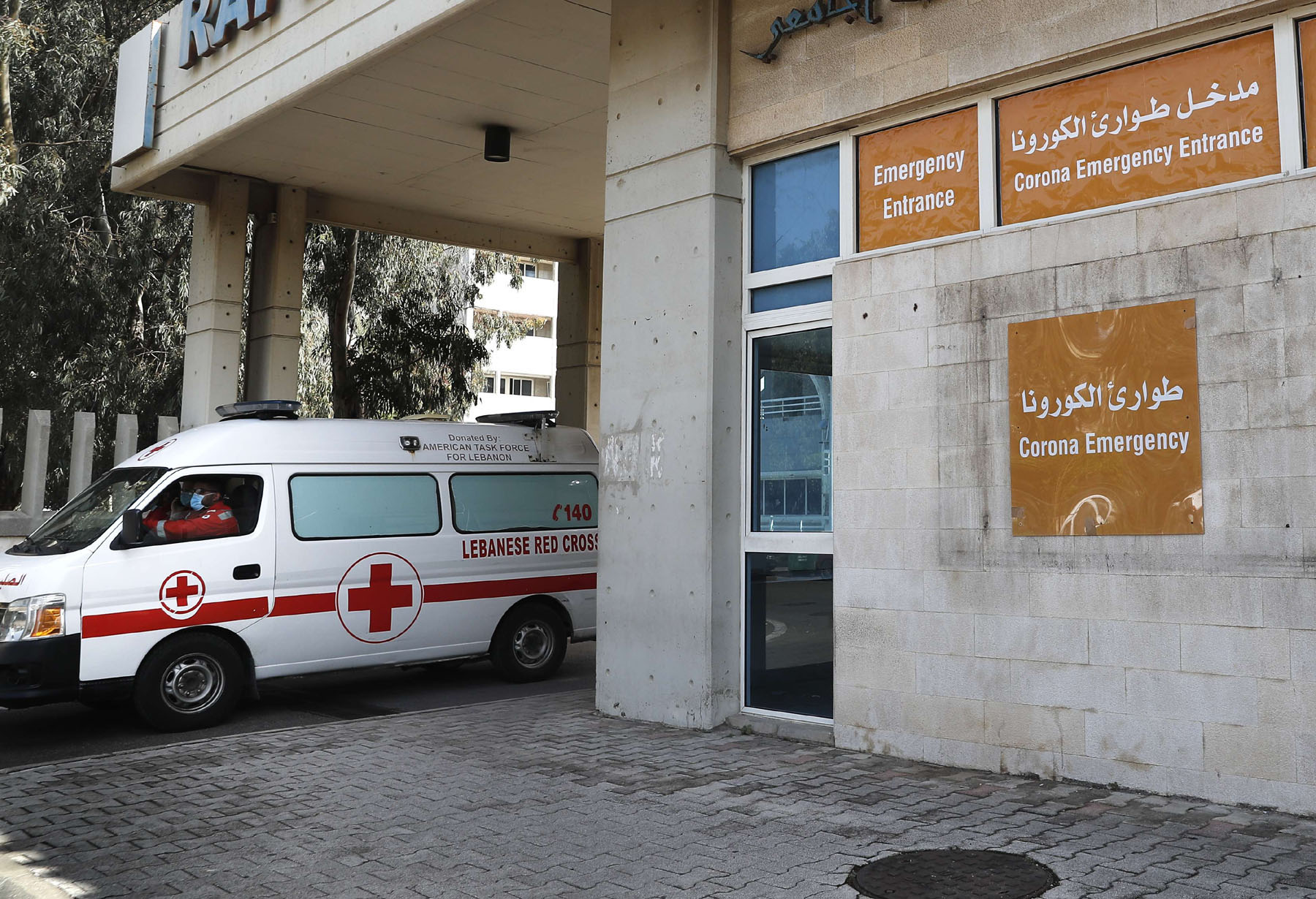 A Lebanese Red Cross ambulance leaves the emergency building of the government-run Rafik Hariri University Hospital, where most Lebanese coronavirus cases are treated, in Beirut, March 11. (AP)