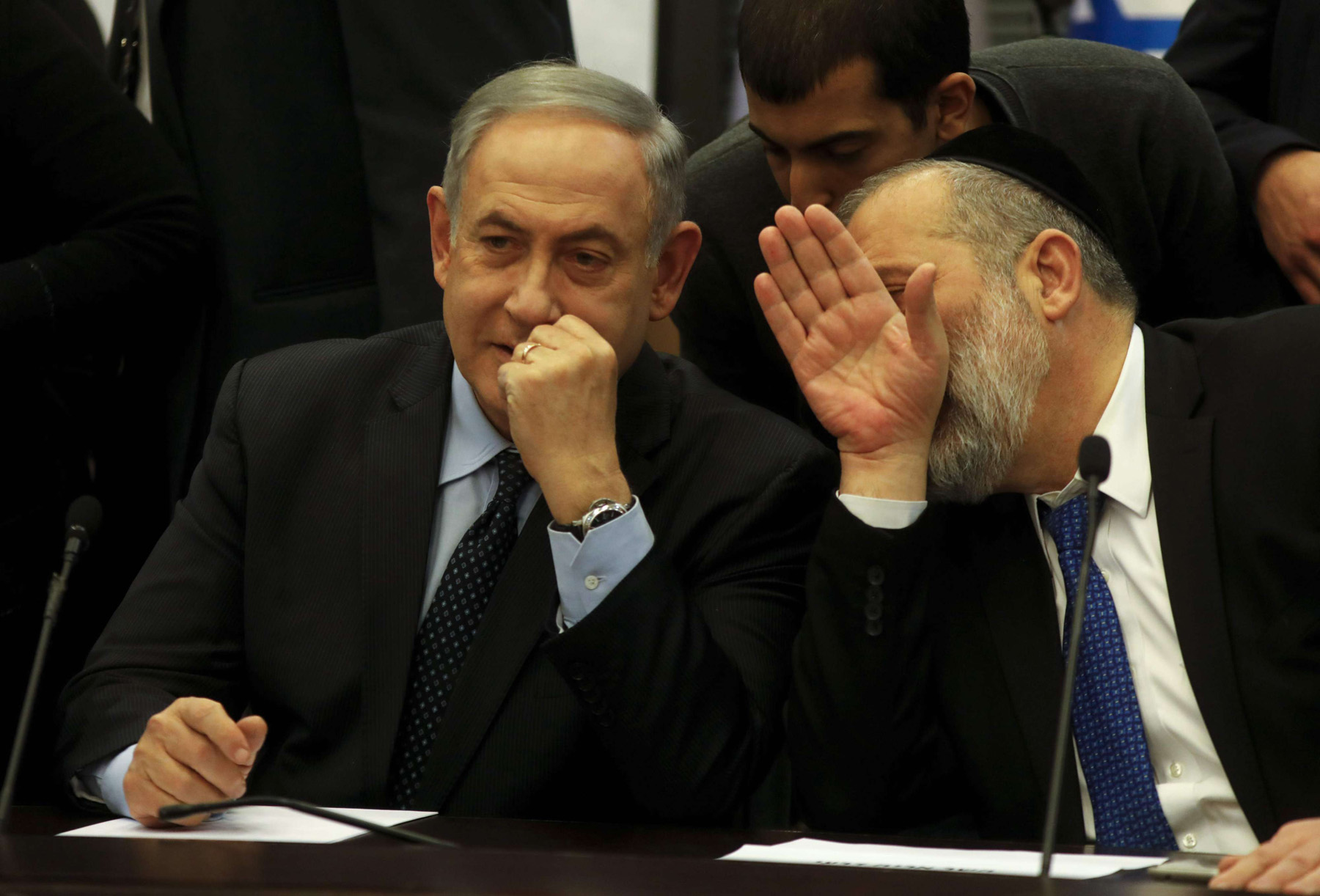 Arye Deri (R), the chairman of Israel's Shas party, whispers to Prime Minister Benjamin Netanyahu during a meeting of the right-wing block at the Knesset in Jerusalem on March 4. (AFP)