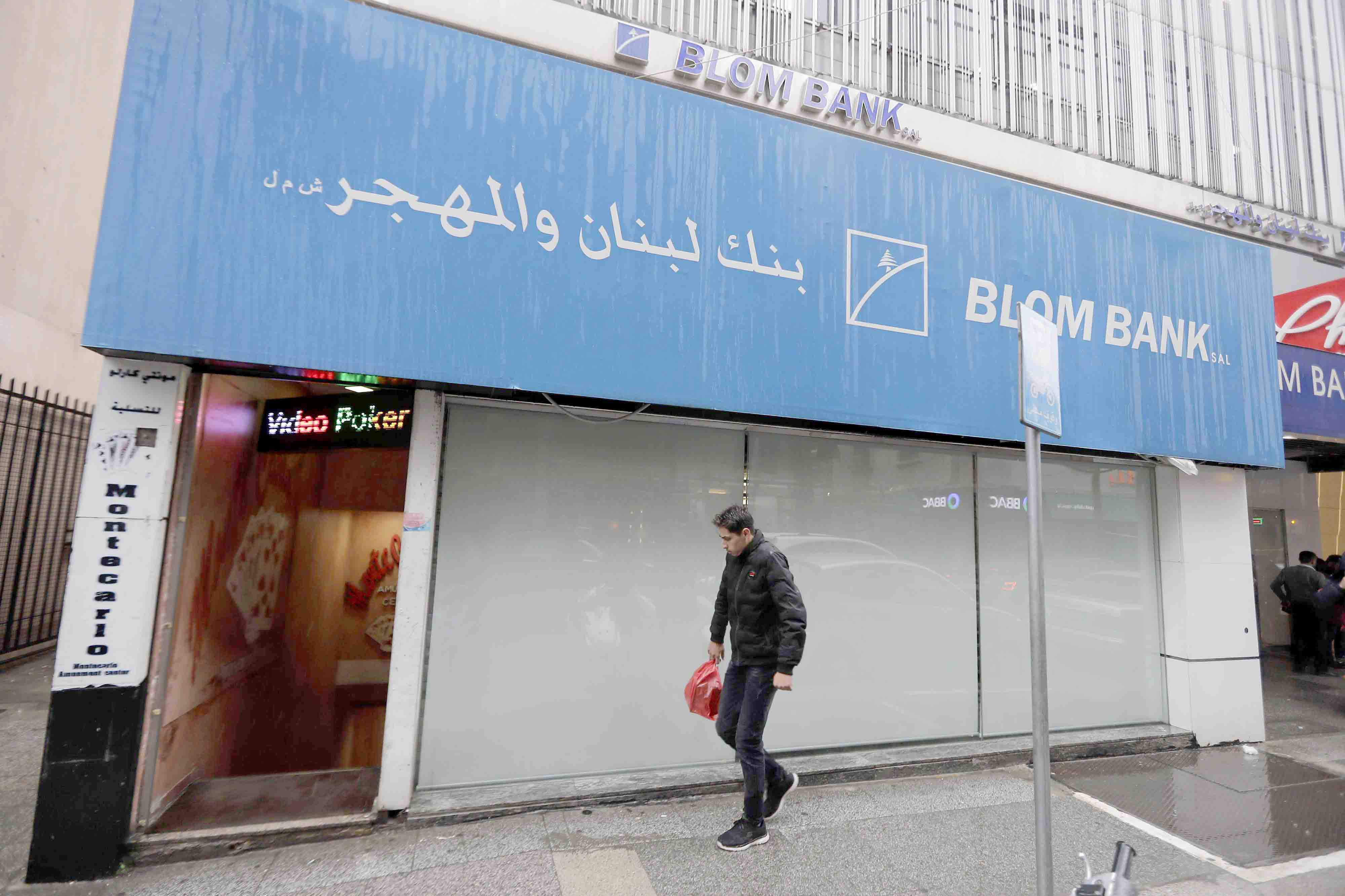 A man walks in front of a bank in Beirut, March 6. (AFP)