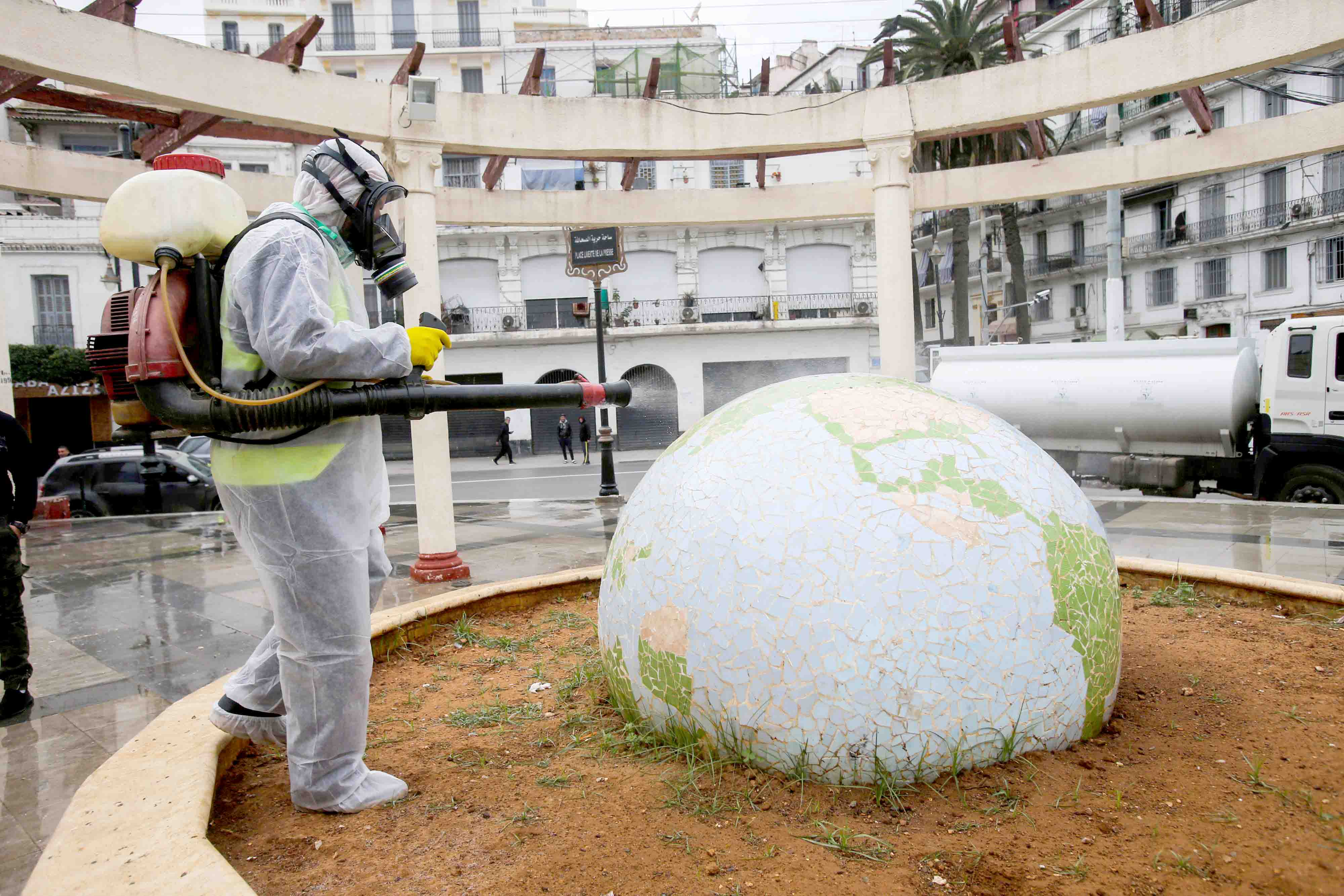 A worker wearing a protective suit disinfects a globe-shaped public garden, following the outbreak of coronavirus disease in Algiers, March 23. (Reuters)