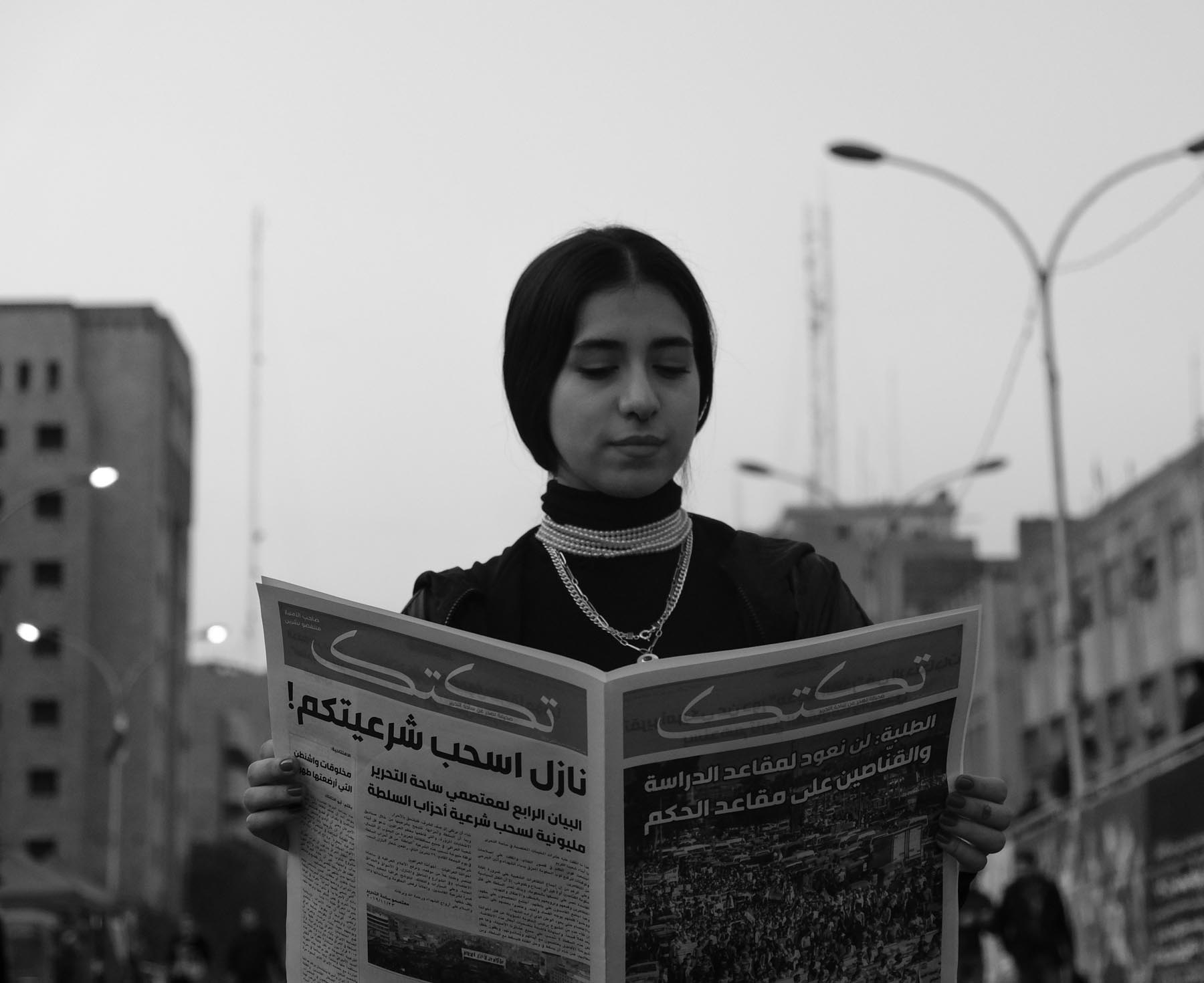 A young woman reads a newspaper near Tahrir Square in Baghdad during protests. (Amir Hazim)