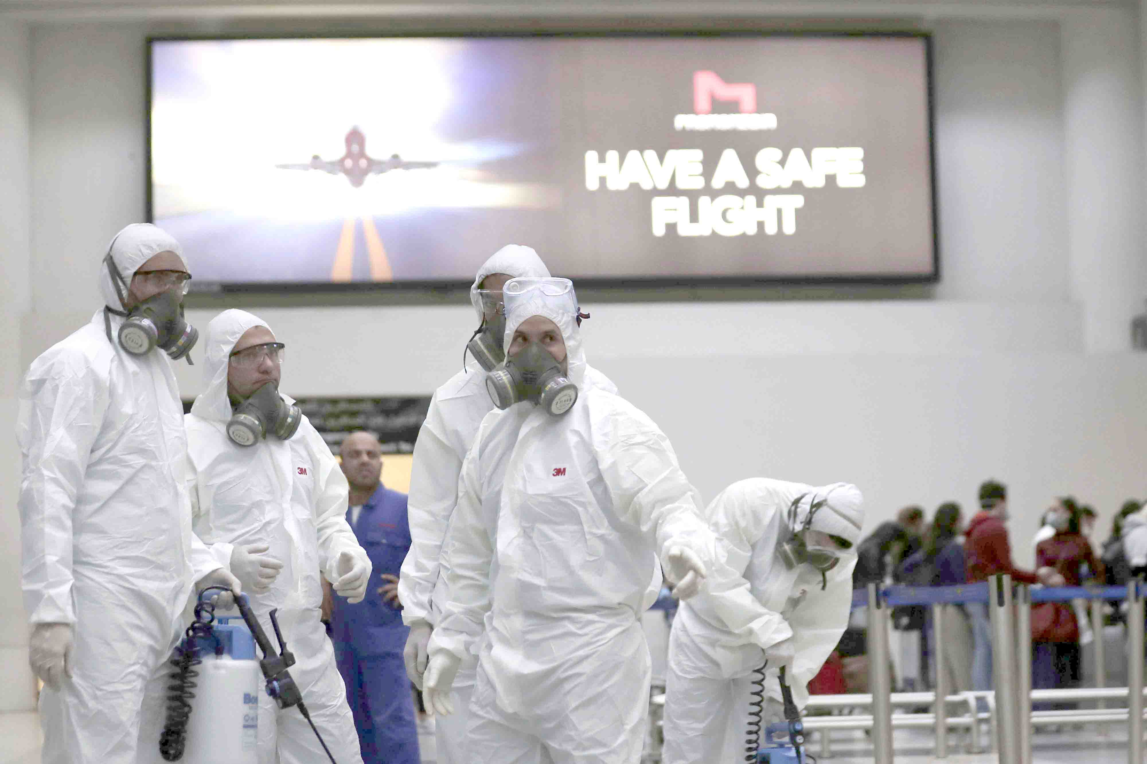 Workers wearing protective gear spray disinfectant as a precaution against the coronavirus outbreak in the departure terminal at the Rafik Hariri International Airport in Beirut, March 5. (AP)