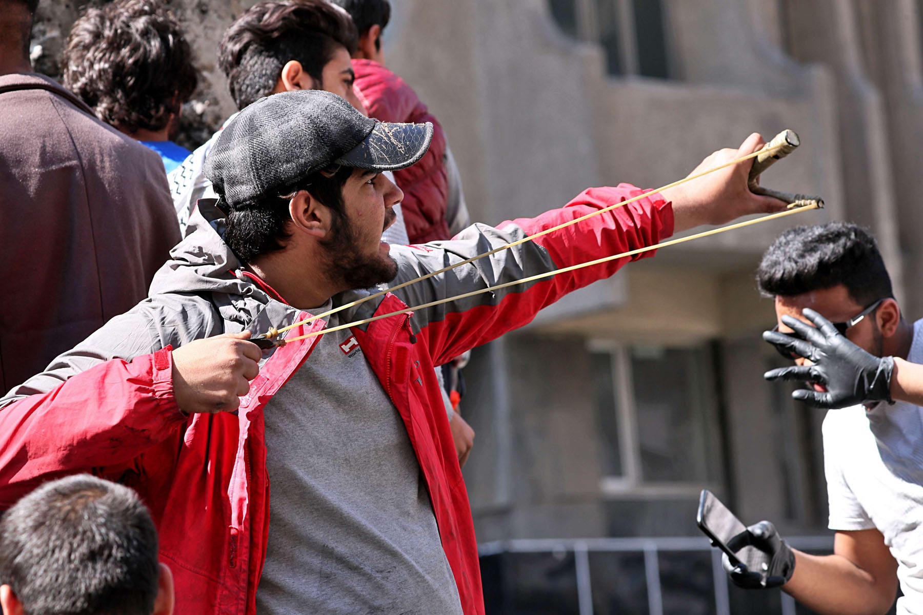 An anti-government protester uses a slingshot to fire a stone at security forces during clashes in Baghdad, March 2. (AP)