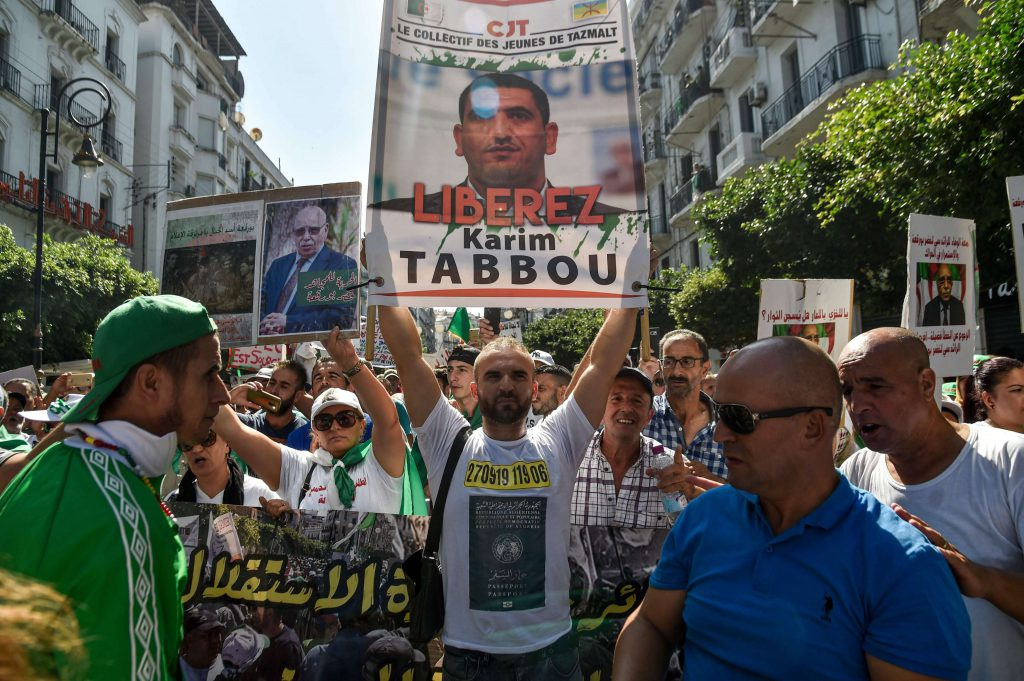 An Algerian protester marches with a sign calling to set free politician Karim Tabbou during a demonstration against the ruling class in the capital Algiers, last September. (AFP)