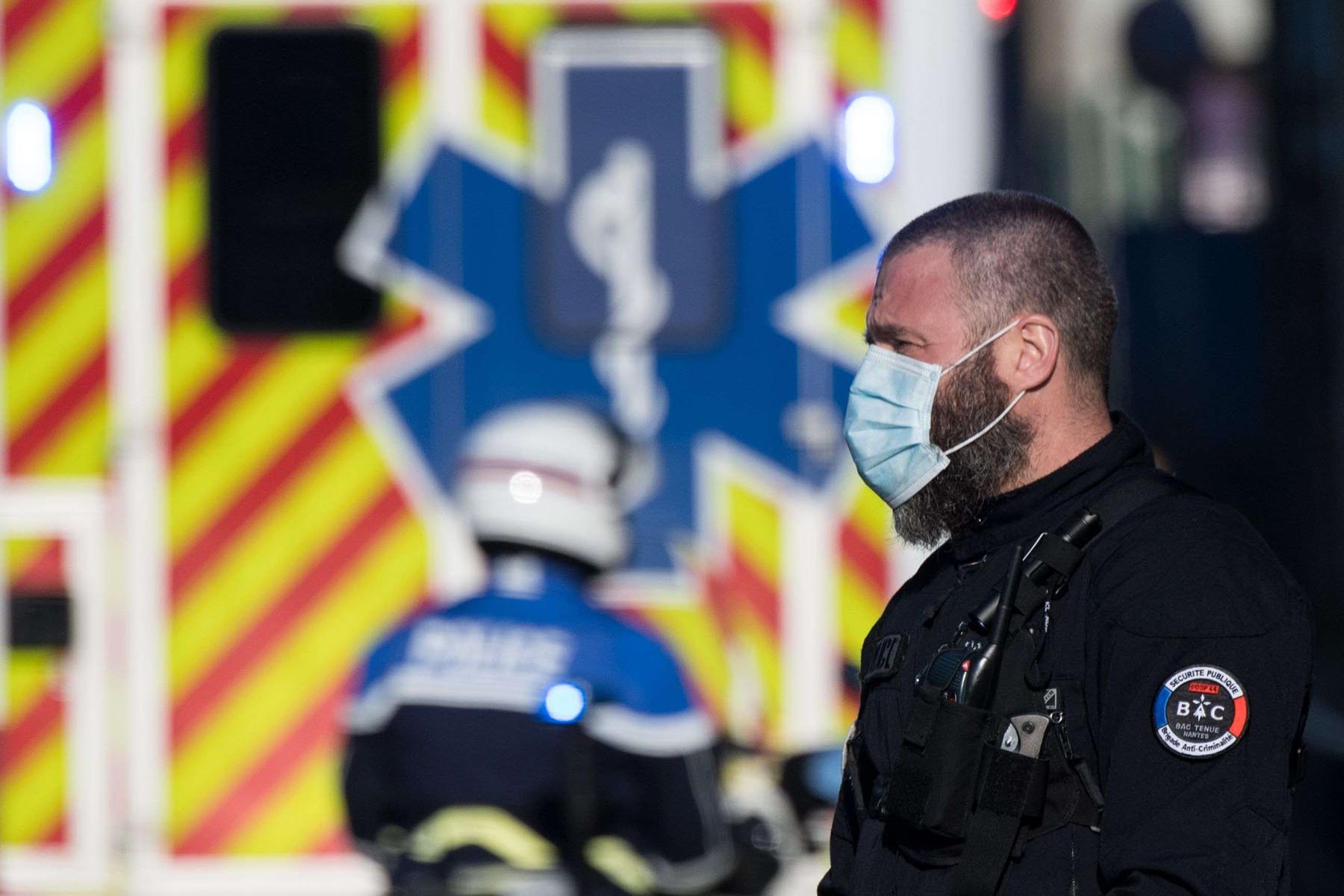 Police officers escort an ambulance arriving to take care of patients infected with the covid-19 disease, on March 26 in Nantes. (AFP)