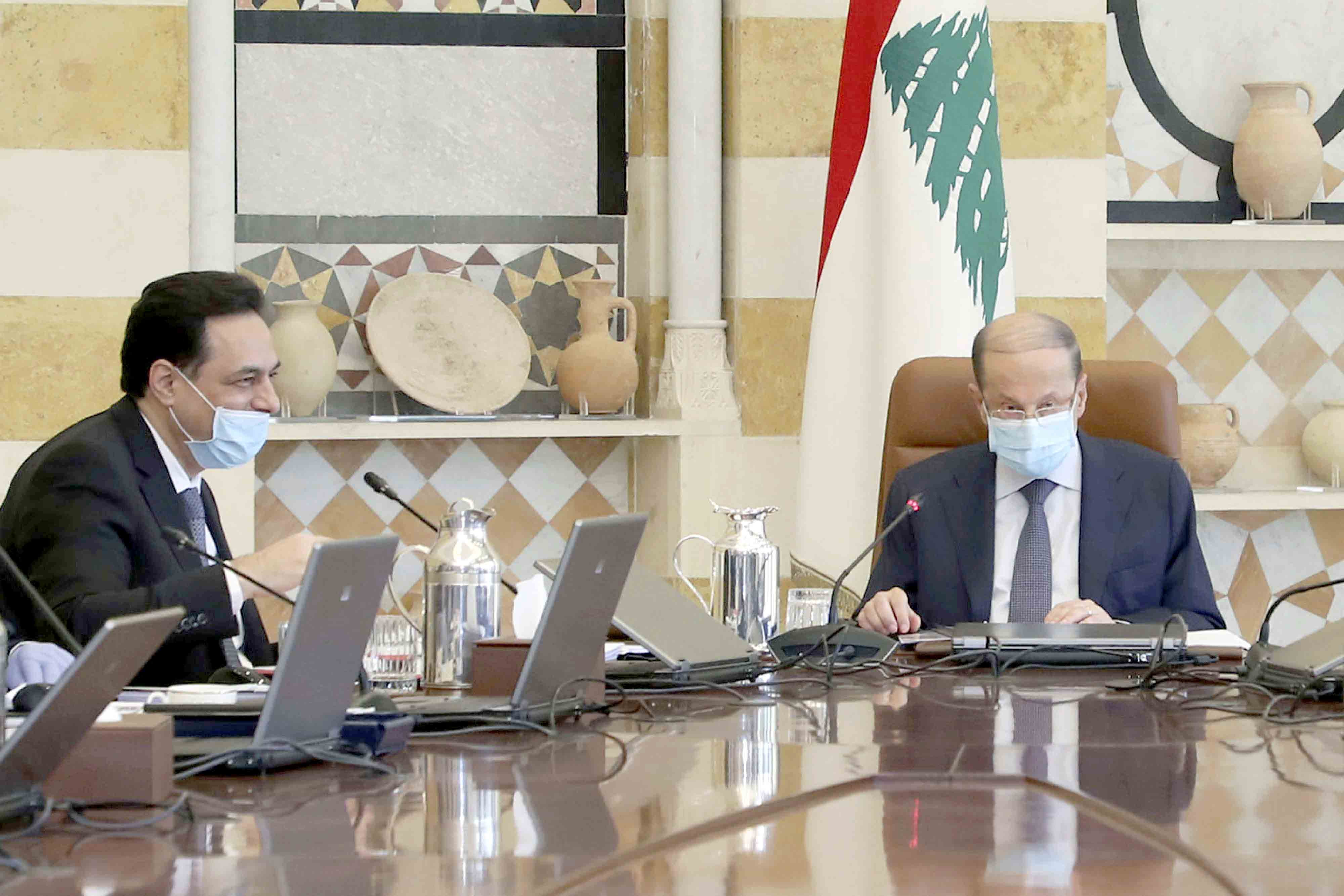 Lebanese President Michel Aoun (R) and Prime Minister Hassan Diab attend a cabinet meeting at the presidential palace in Baabda, east of Beirut, March 19. (AP)