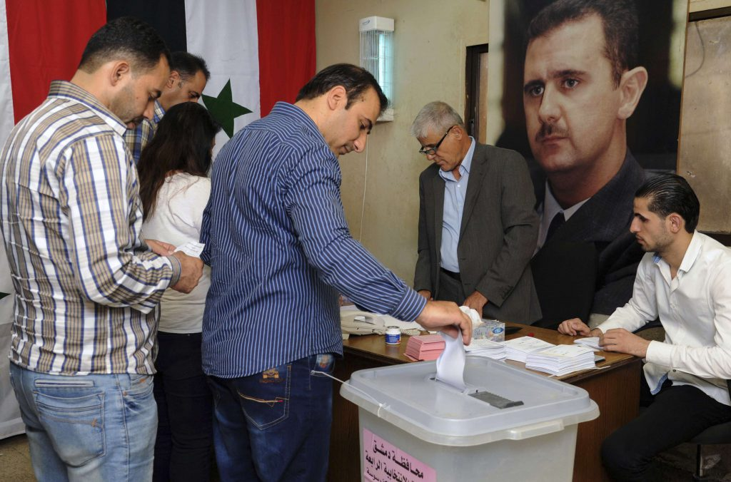 Syrians cast their votes at a polling station during municipal elections, in Damascus, Syria, Sunday, Sept 16, 2018.