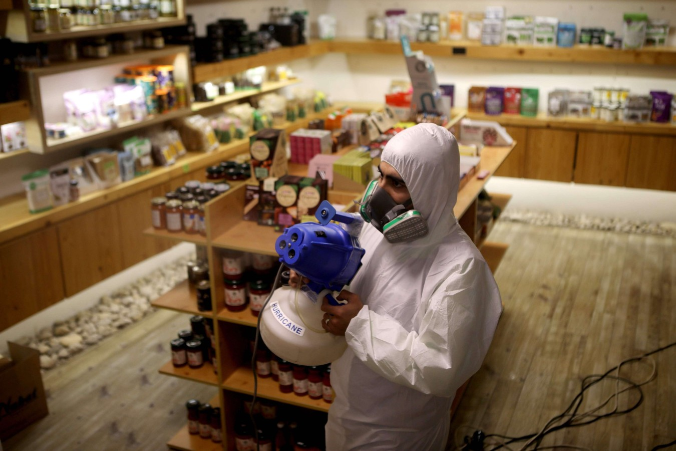 A sanitary worker disinfects a supermarket in the Lebanese capital Beirut on March 19, 2020, amid measures to contain the spread of the novel coronavirus. (AFP)