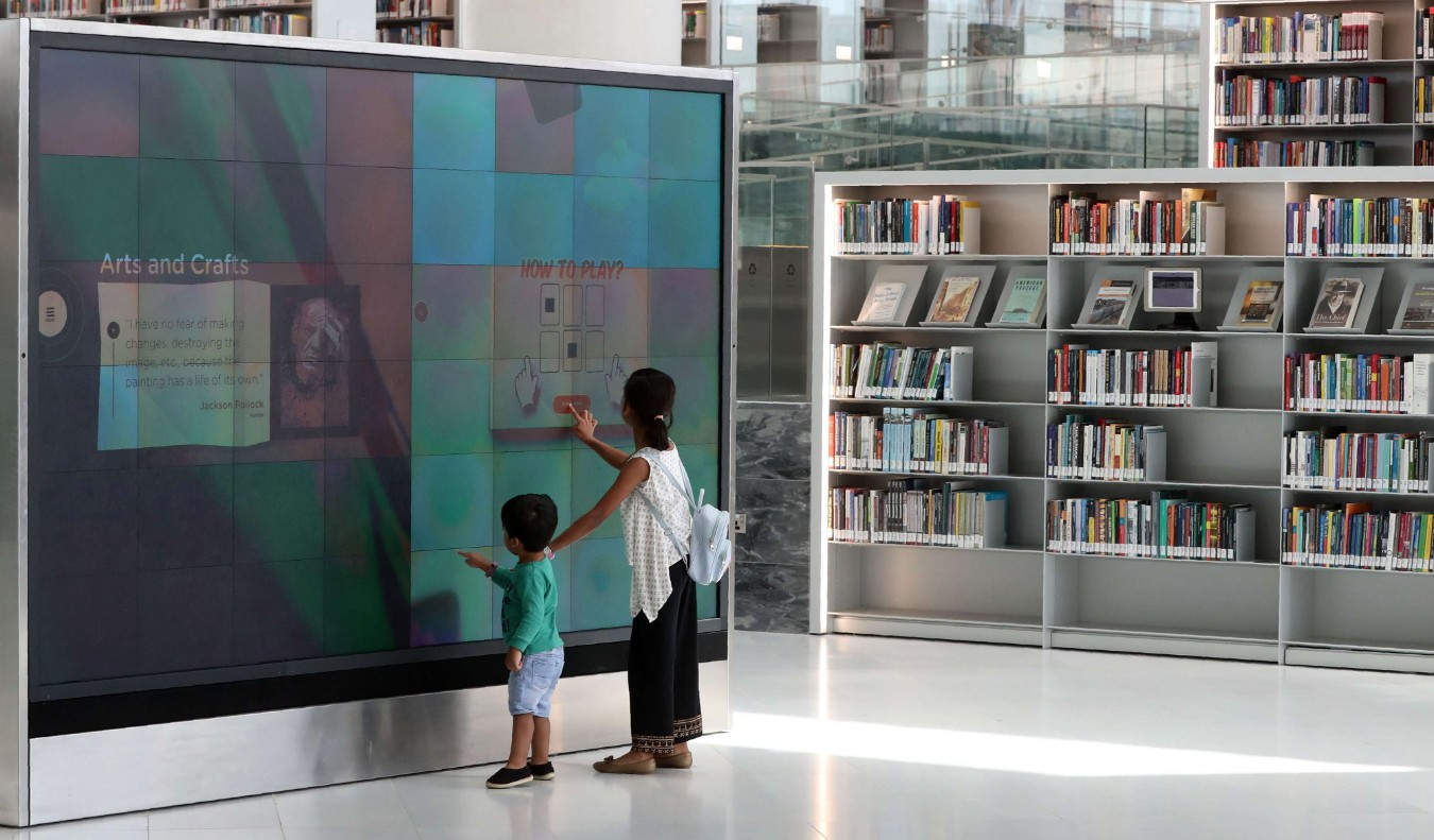 A girl and a boy use a giant interactive display screen at the Qatar National Library in the capital Doha on May 19, 2019. (AFP)