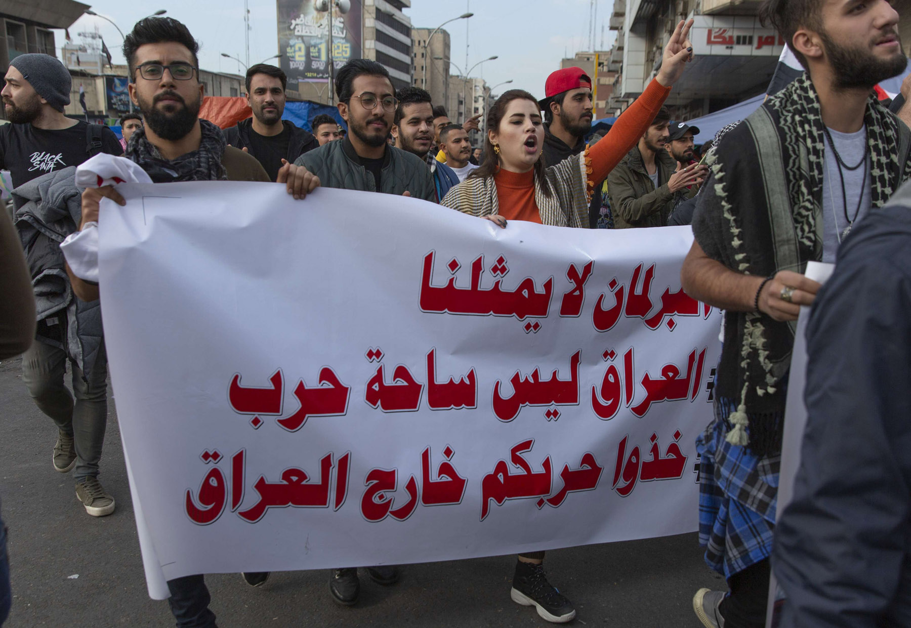 "Iraqi demonstrators carry a poster that reads in Arabic, ""the parliament does not represent us, Iraq is not a war theatre take your wars out of Iraq,"" during protests in Baghdad. (AP)"