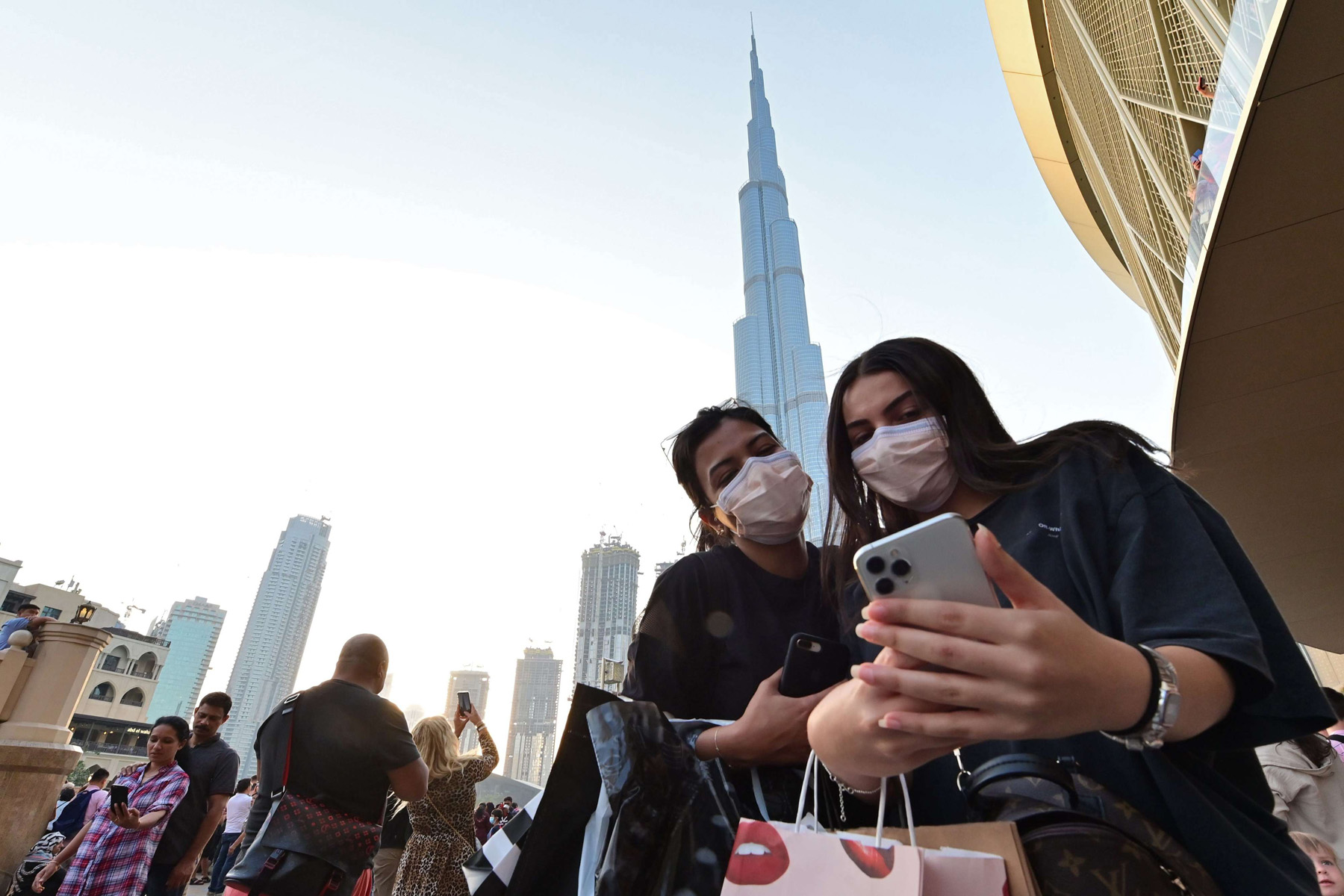 "Women wearing protective masks pose for a ""selfie""  in front of Burj Khalifa in Dubai. (AFP)"