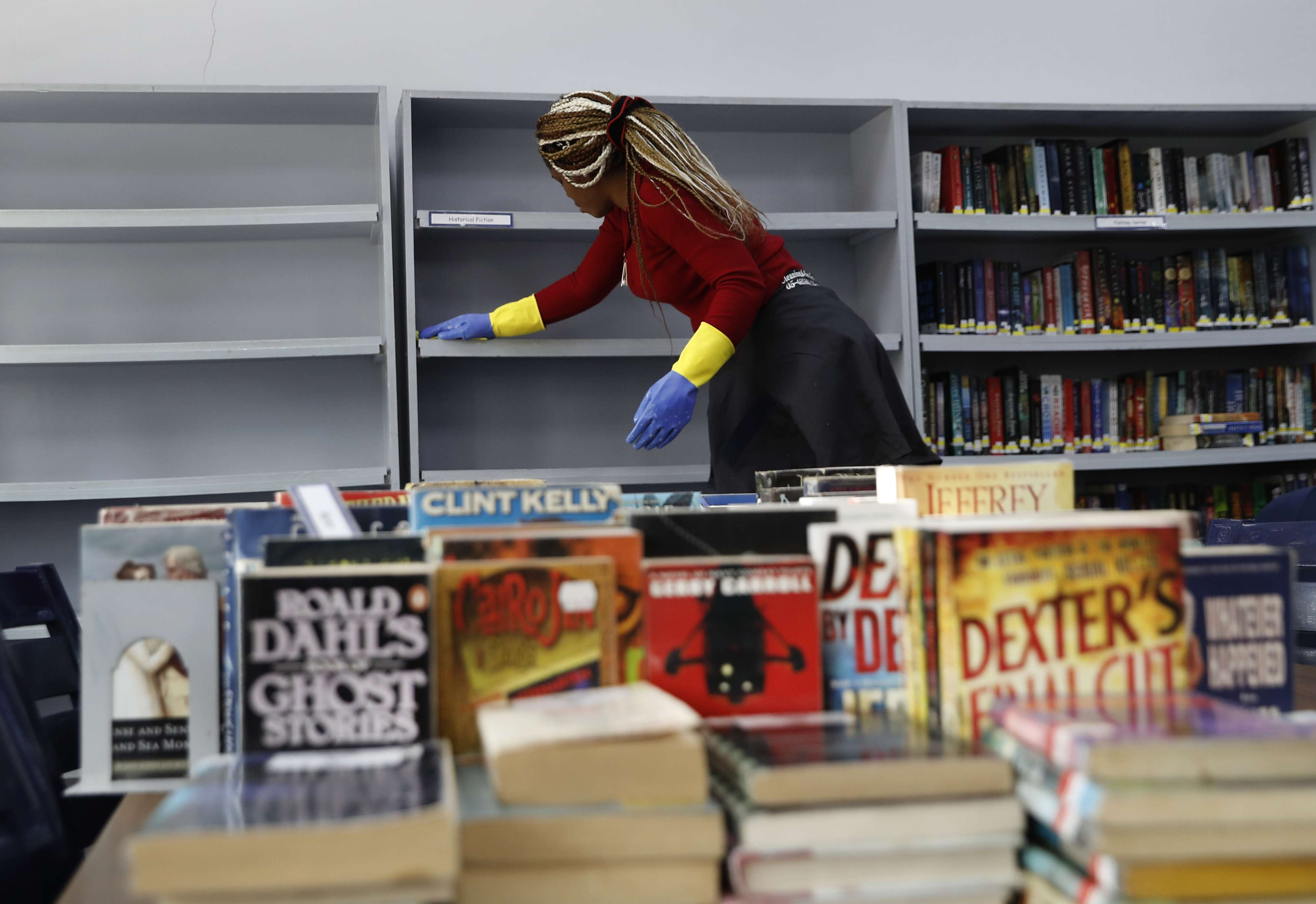 A worker disinfects bookshelves as part of a sterilisation campaign against the new coronavirus, at the library of the Evangelical School, in Loueizeh, east of Beirut, Lebanon, Monday, March 2, 2020. (AP)