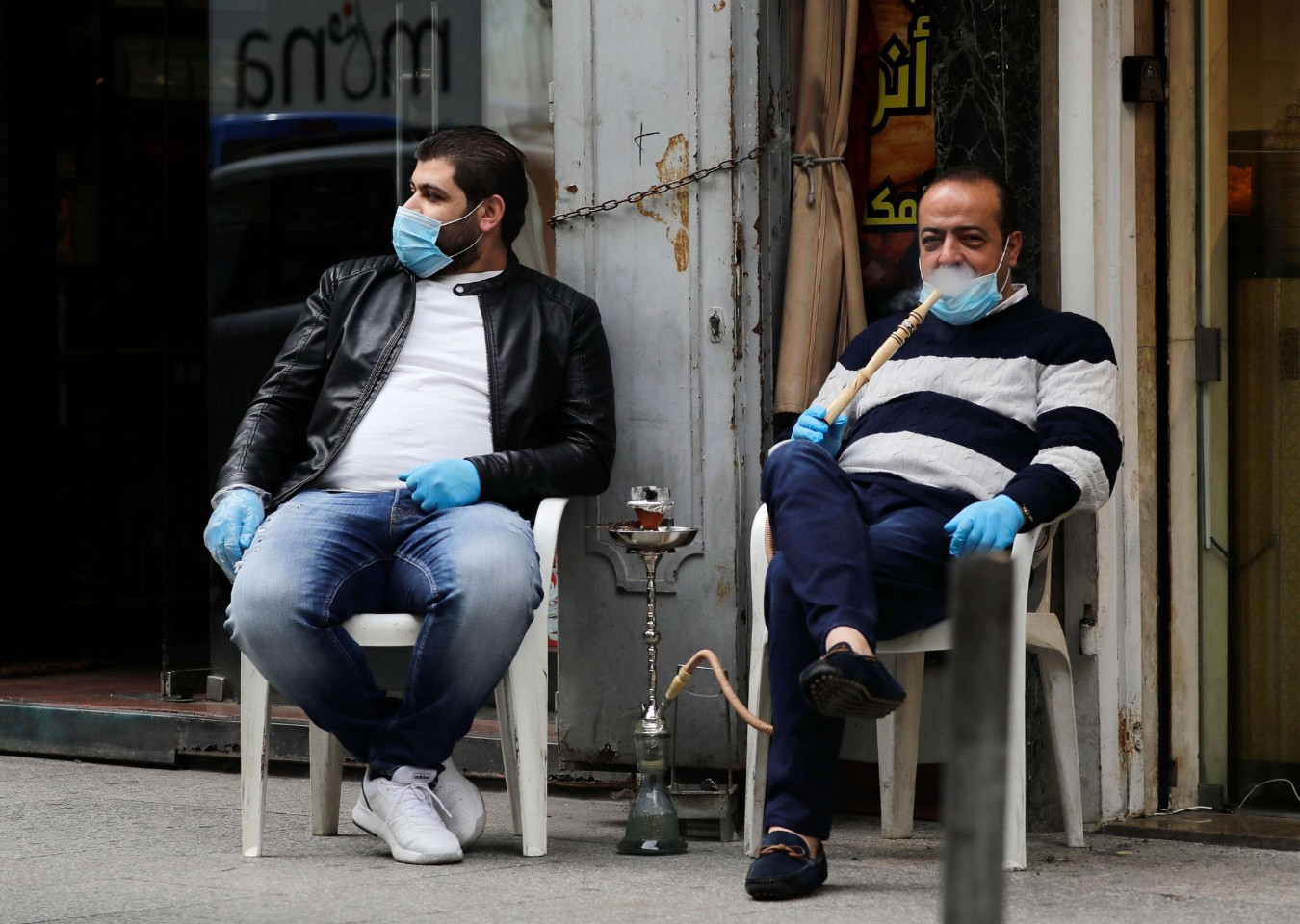 Lebanese men wearing protective masks smoke water pipe or nargileh in Beirut on March 12. (AFP)
