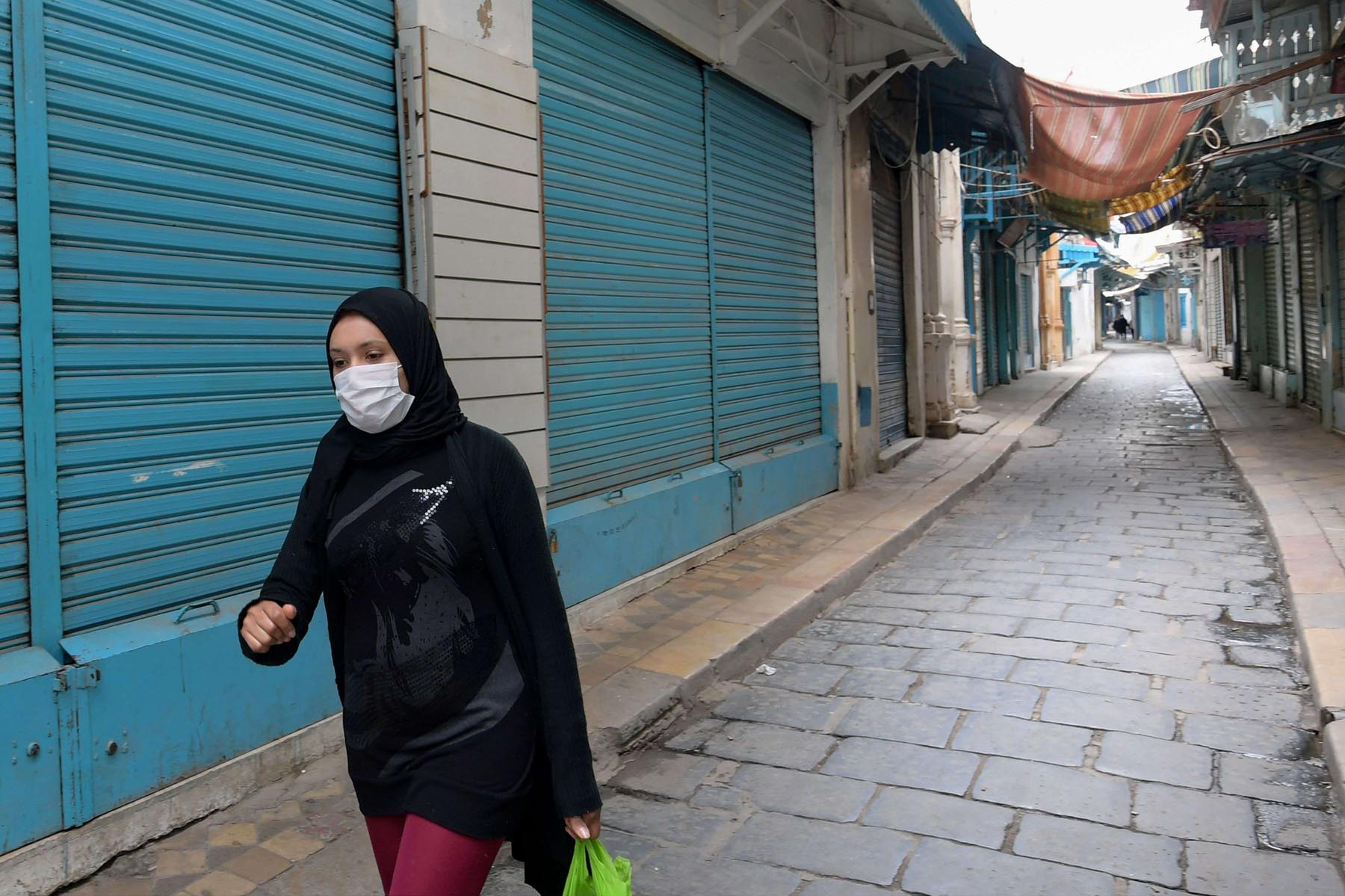 A Tunisian woman wearing a protective face mask walks through an alley in the souk of the Medina, on the first day of a general confinement imposed by the authorities in order to stem the spread of the novel cononavirus. (AFP)