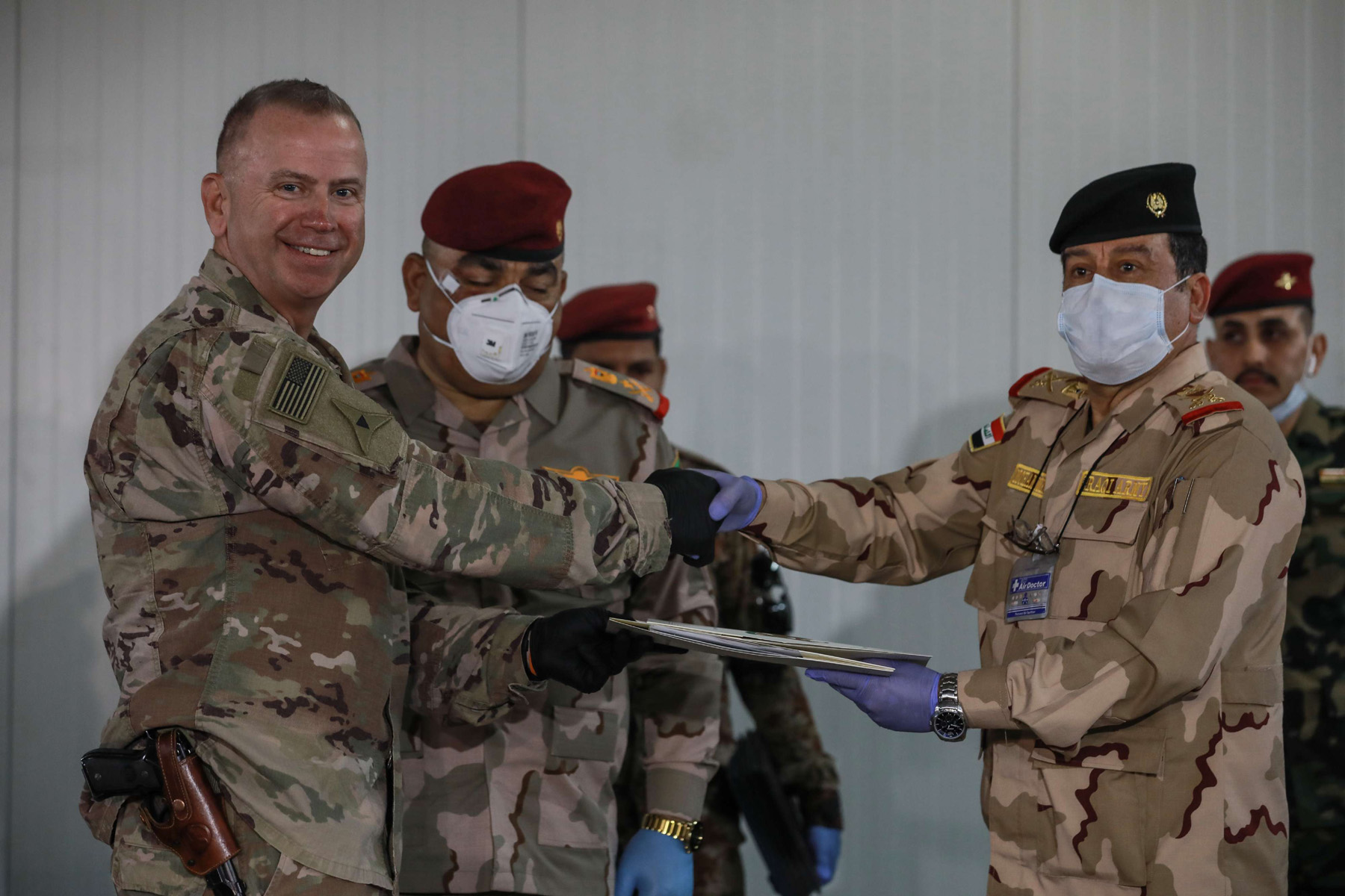 US Brigadier General Vincent B. Barker (L) shakes hands with Iraq's Staff Major General Mohammad Fadhel Abbas during the handover ceremony of the K1 air base near Kirkuk in northern Iraq, last March. (DPA)