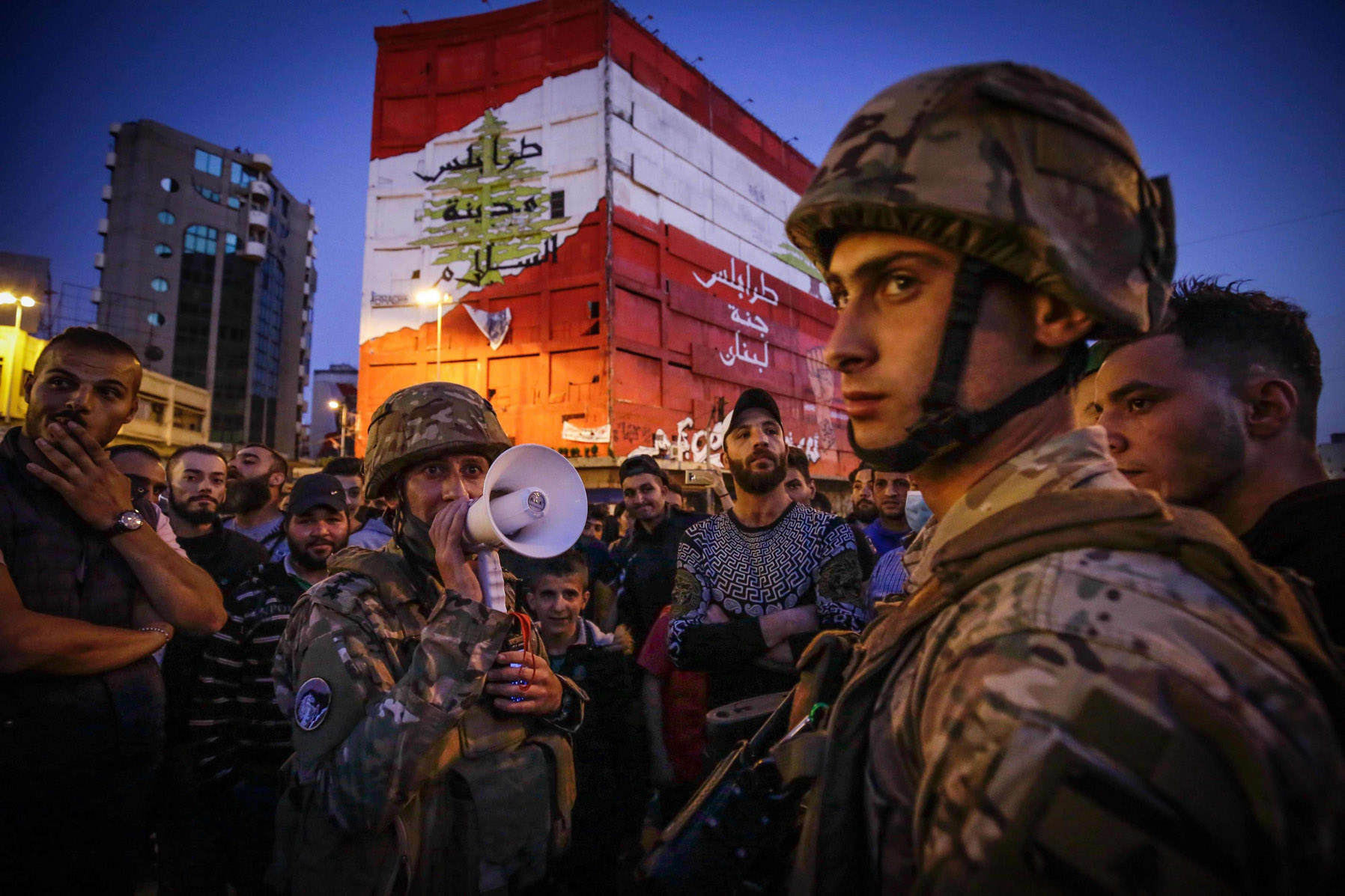 Lebanese soldiers keep watch as several hundred people protest in the northern city of Tripoli on April 17, despite the country's coronavirus lockdown. (AFP)