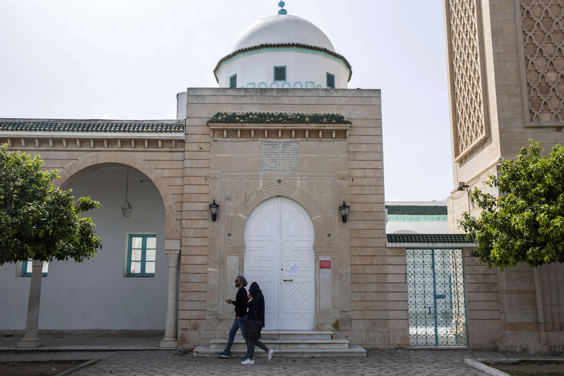 People walk past a closed mosque outside Tunis. (AP)