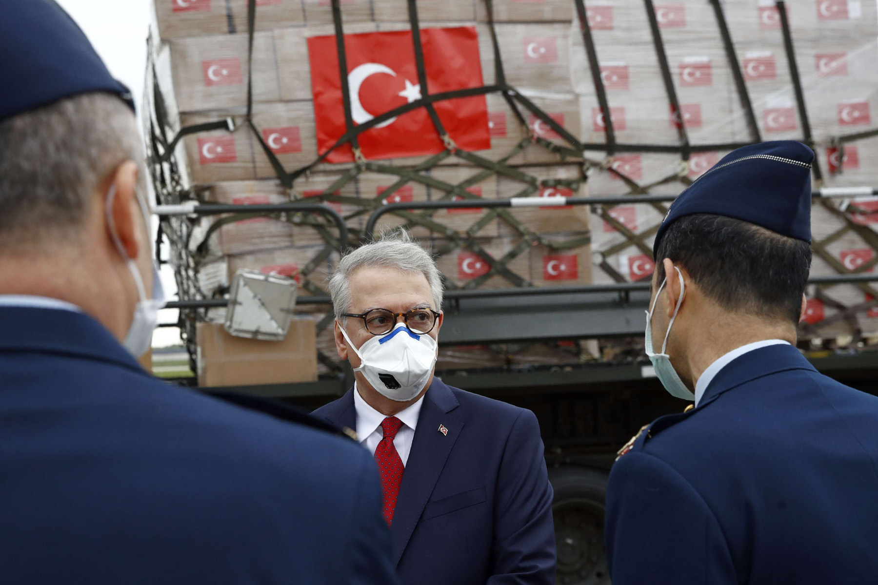 Turkish Ambassador to the United States, center, stands on a tarmac as a military aircraft carrying a donation of medical supplies from Turkey is unloaded, April 28, 2020, at US Andrews Air Force Base, Maryland. (AP)