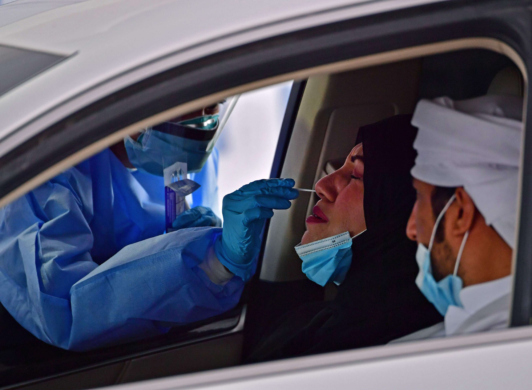 A nurse uses a swab to test the passenger of a car for COVID-19 at a drive-through verification centre in the Emirati capital Abu Dhabi, April 2. (AFP)