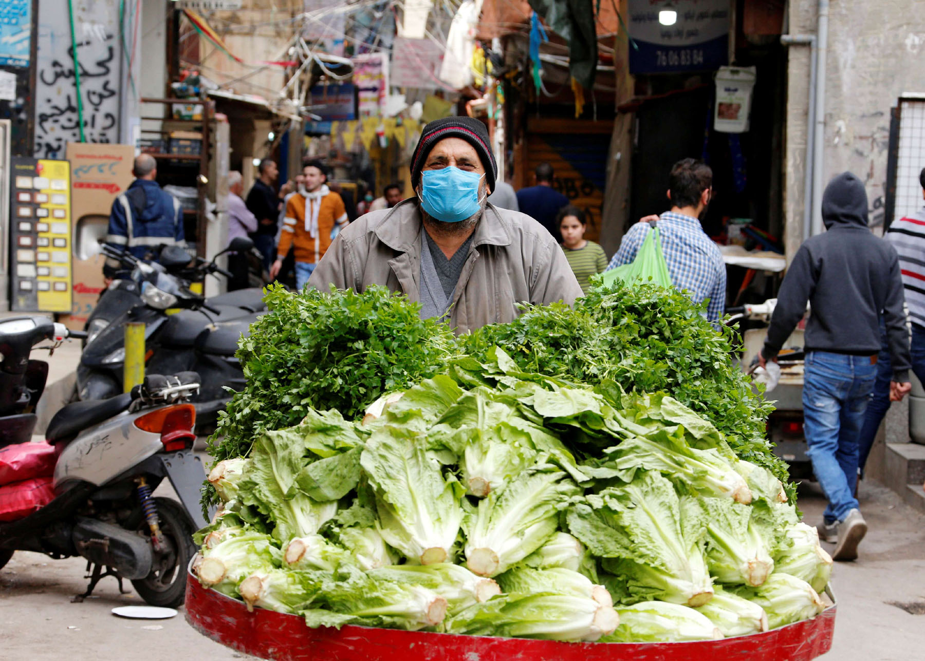 A street vendor wearing a face mask pushes his cart in Shatila Palestinian refugee camp in Beirut's suburbs, last March. (Reuters)