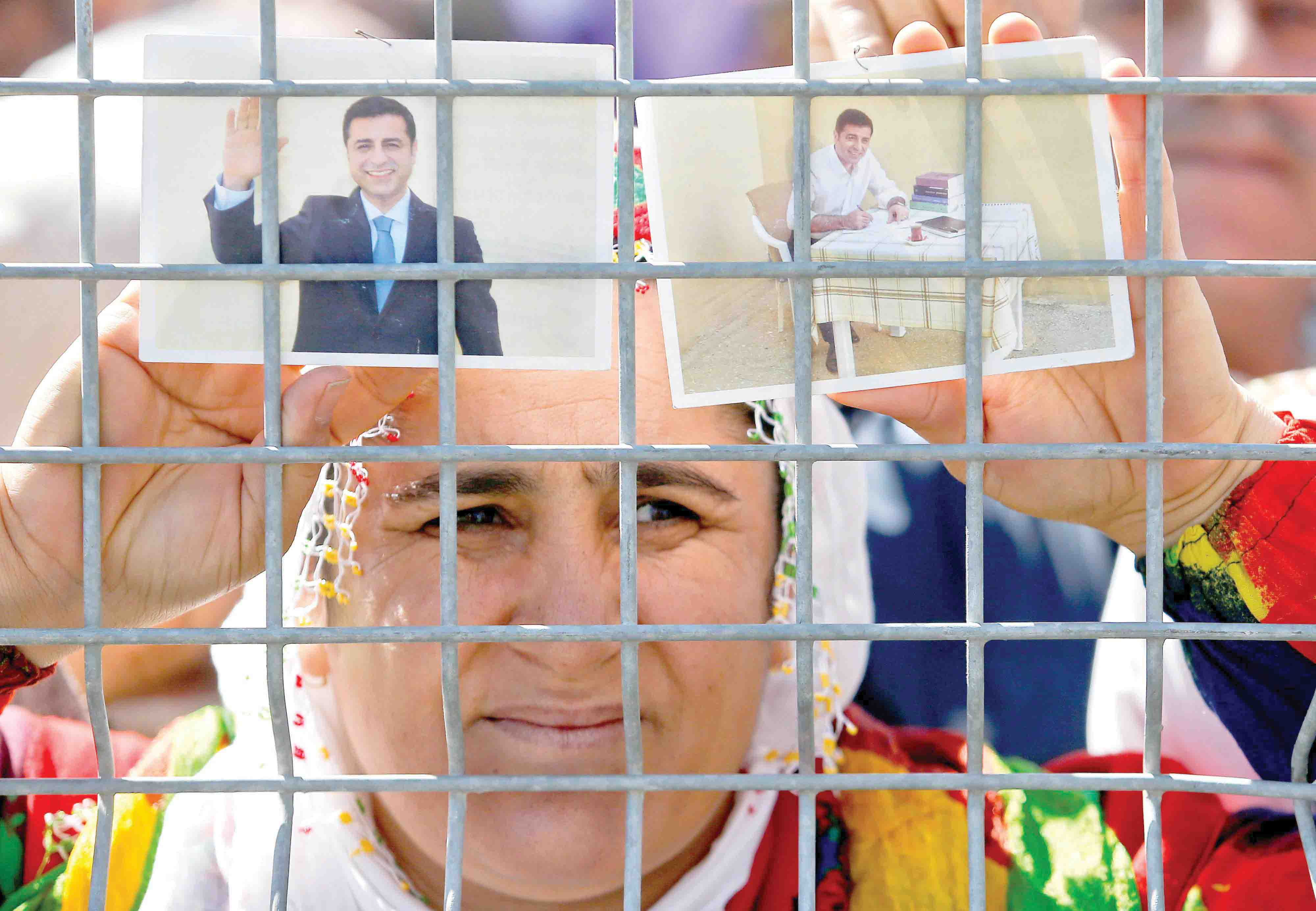 A woman holds pictures of jailed former leader of Turkey's main pro-Kurdish Peoples' Democratic Party Selahattin Demirtas.(Reuters)