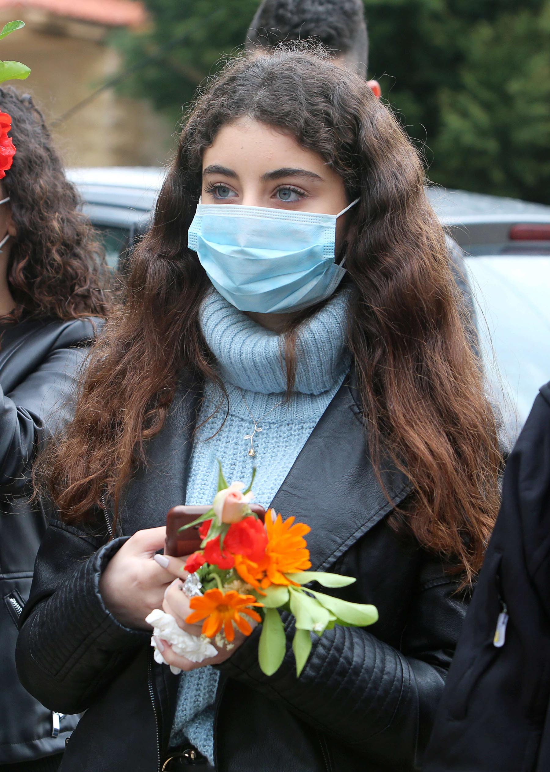 A Lebanese woman wearing a protective mask holds flowers as she takes part in a re-enactment of the crucifixion of Jesus Christ during Good Friday, April 10.  (Reuters)