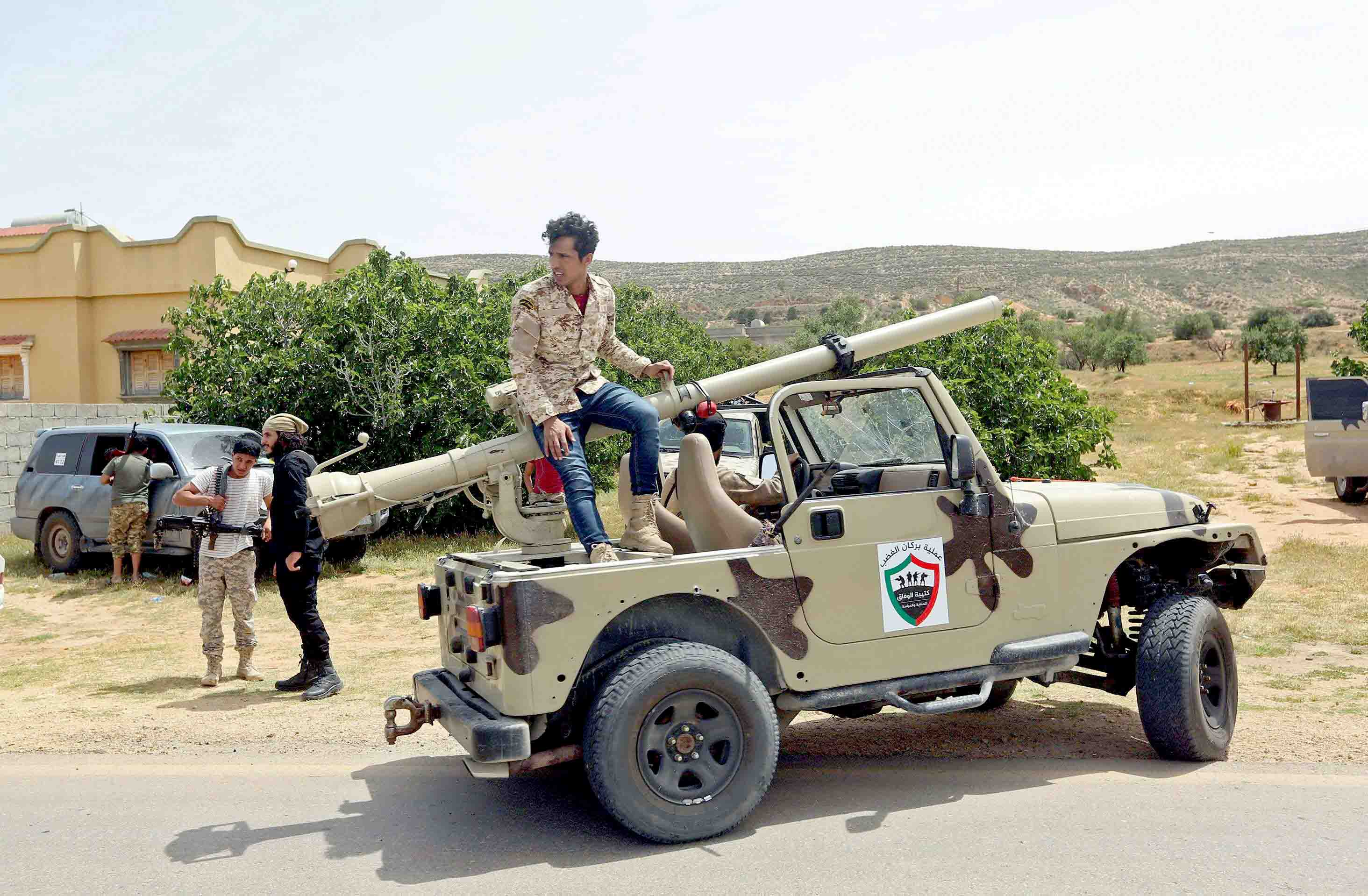 Fighters with Libya's Government of National Accord (GNA) gather at a position near the town of Garabulli, some 70km east of the capital Tripoli. (AFP)