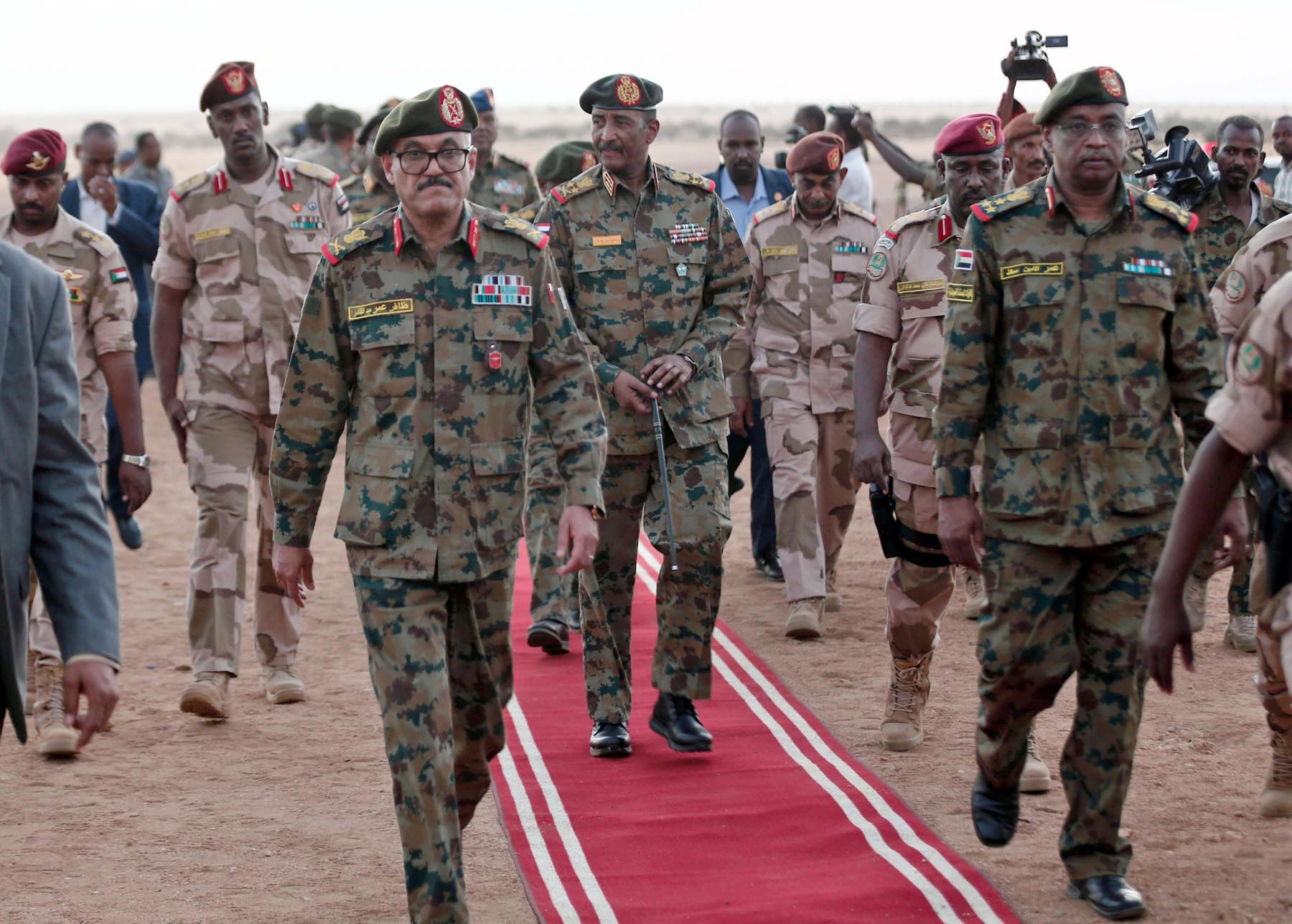President of the Sudanese Transitional Council General Abdel Fattah al-Burhan (C) walks alongside military officers during an army exercise on the outskirts of the capital Khartoum, last October (AFP)
