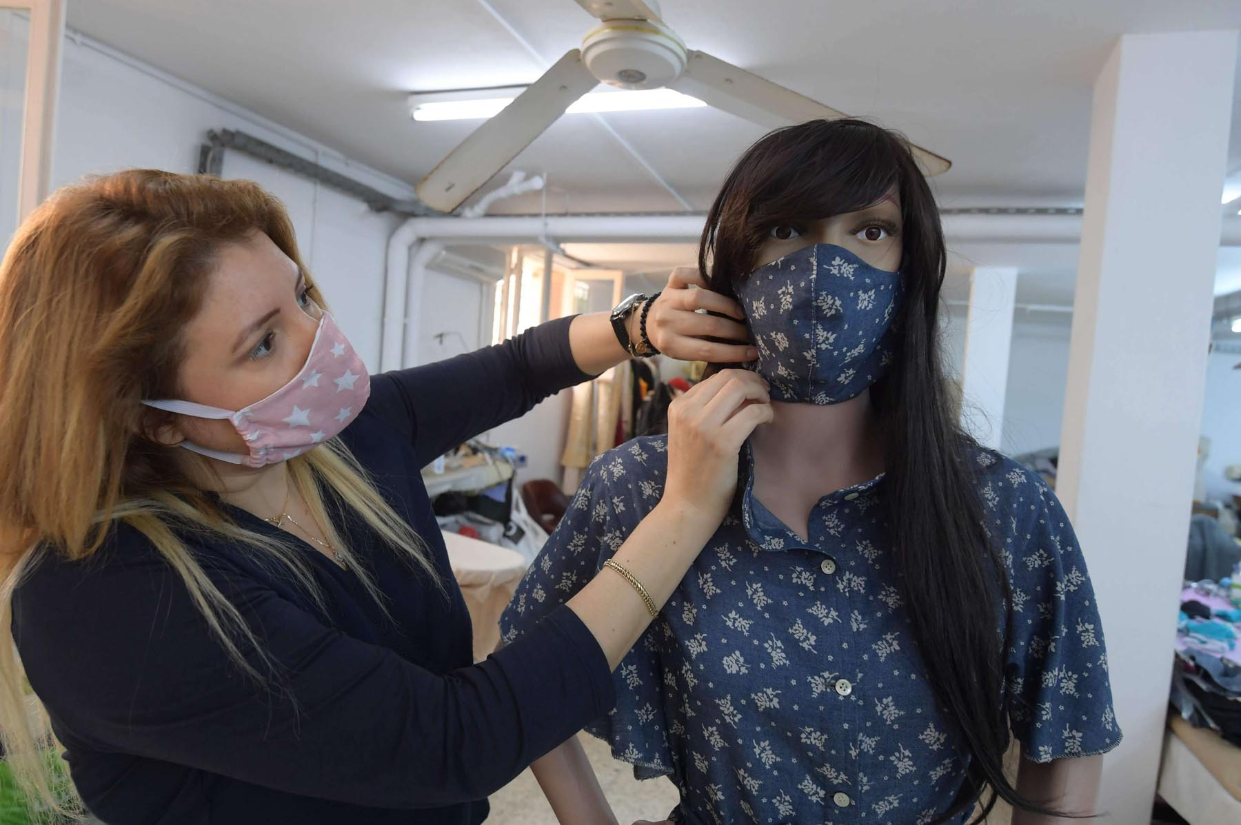 Tunisian designer Myriam Riza adjusts an embellished protective mask on a mannequin at the Tunis workshop of her haute couture Miss Anais brand, which donates masks daily to staff at hospitals that care for COVID-19 patients. (AFP)