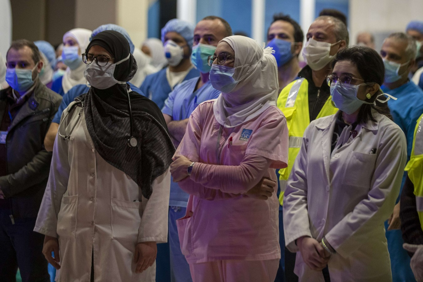 Health workers of government-run Rafik Hariri University Hospital, where most of the Lebanese coronavirus cases are treated, are saluted by Lebanese policemen. (AP)
