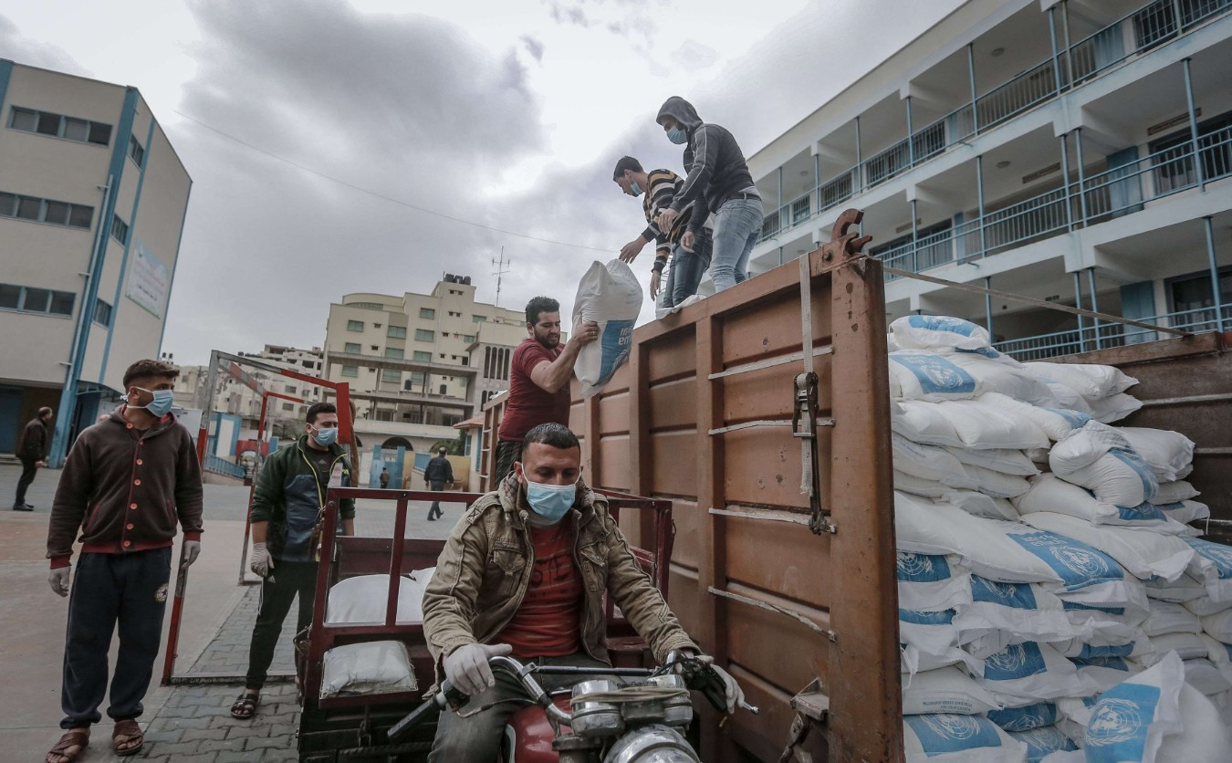 Palestinian employees of the United Nations Relief and Works Agency for Palestine Refugees in the Near East (UNRWA), wearing surgical masks and gloves, divide food aid rations and place them onto transport vehicles. (dpa)