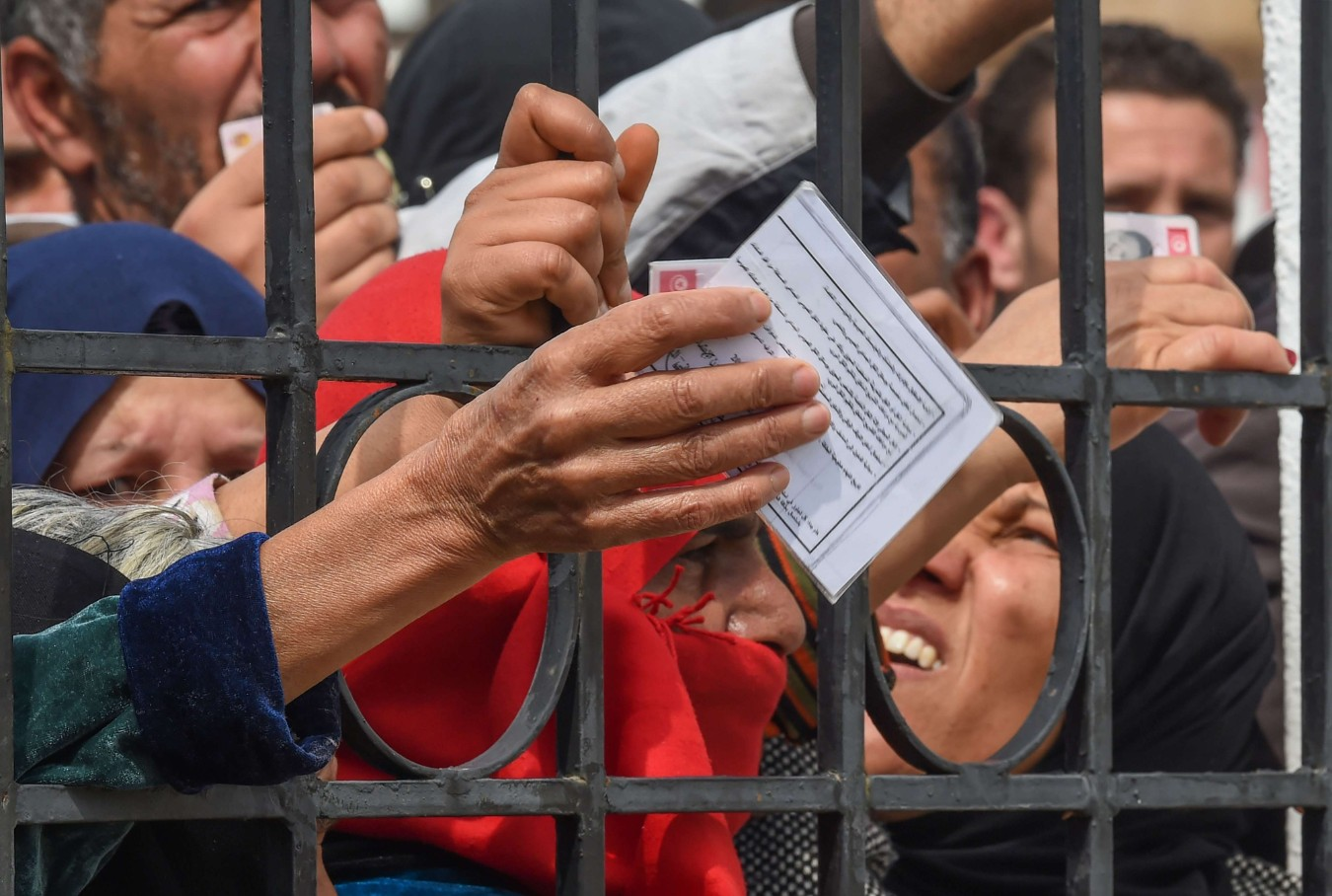 Needy Tunisian citizens gather with their identification cards in Mnihla district outside of Tunis on March 30, clamouring for financial aid promised by the government. (AFP)