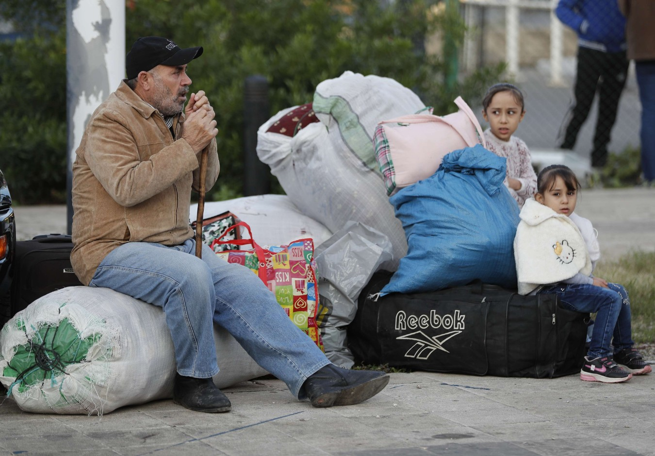 A Syrian refugee sits next to his belongings as he waits to board a bus to take him home to Syria, in Beirut, Lebanon, Tuesday, Dec. 3, 2019. (AP)