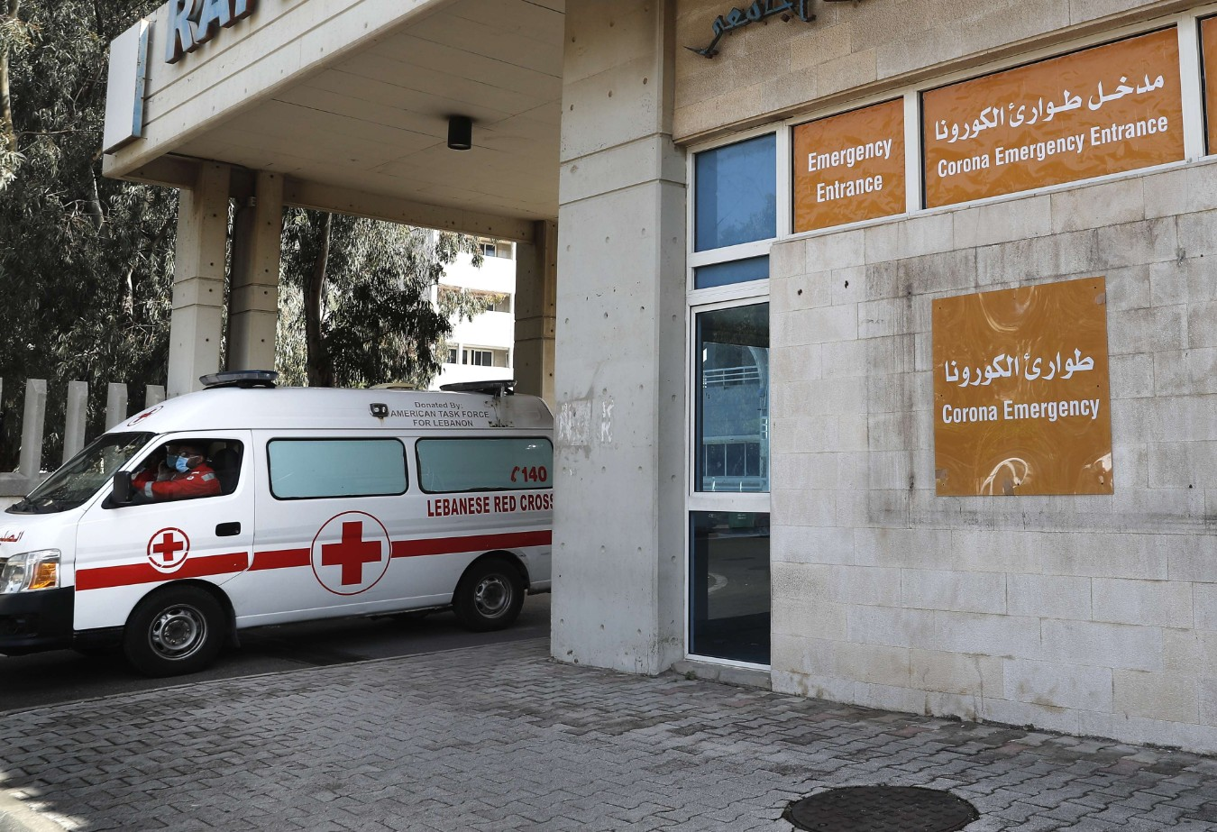 An ambulance of the Lebanese Red Cross leaves the emergency building of the government-run Rafik Hariri University Hospital, where most of the Lebanese coronavirus cases are treated, in Beirut, Lebanon,  March 11. (AP)