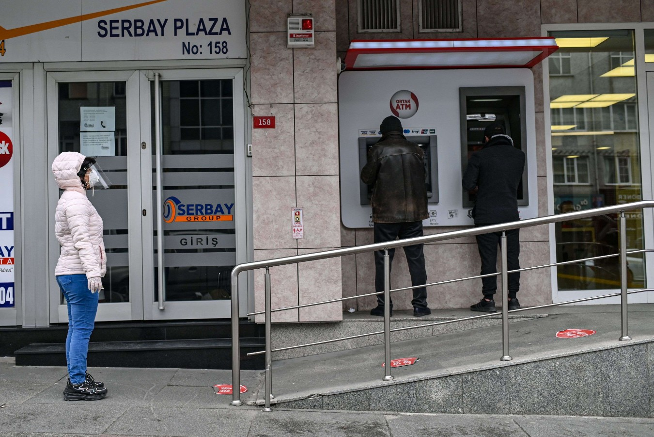 Customers queue outside a bank in Istanbul on April 21. (AFP)