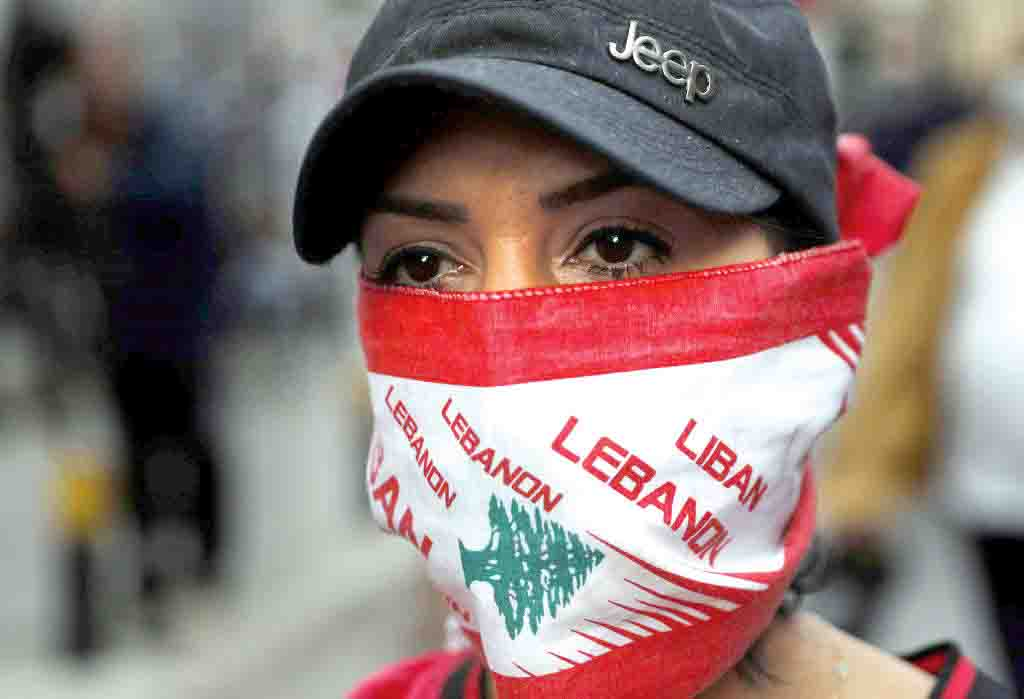 An anti-government protester covers her face with a Lebanese flag during a protest against the Lebanese Central Bank's Governor Riad Salameh and against the deepening financial crisis, in Beirut, April 23. (AP)