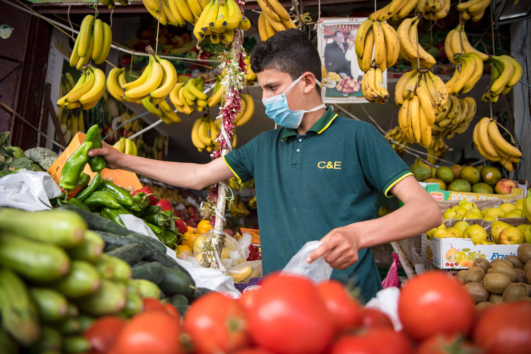 A Moroccan vendor, wearing a protective mask, works at the central market  in the Moroccan capital Rabat. (AFP)
