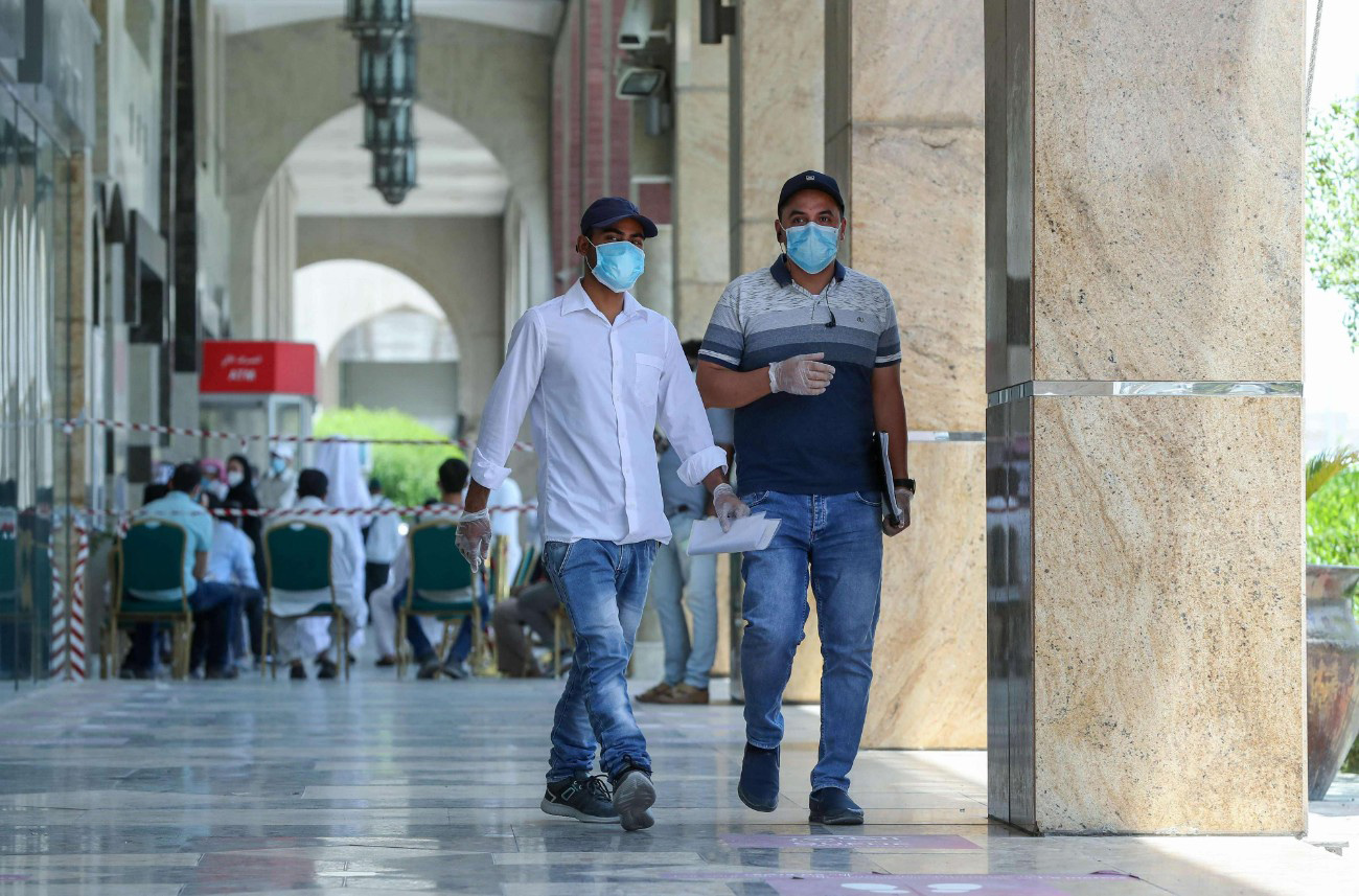 People wearing protective gear walk by on a street of Qatar's capital Doha, on May 17. (AFP)